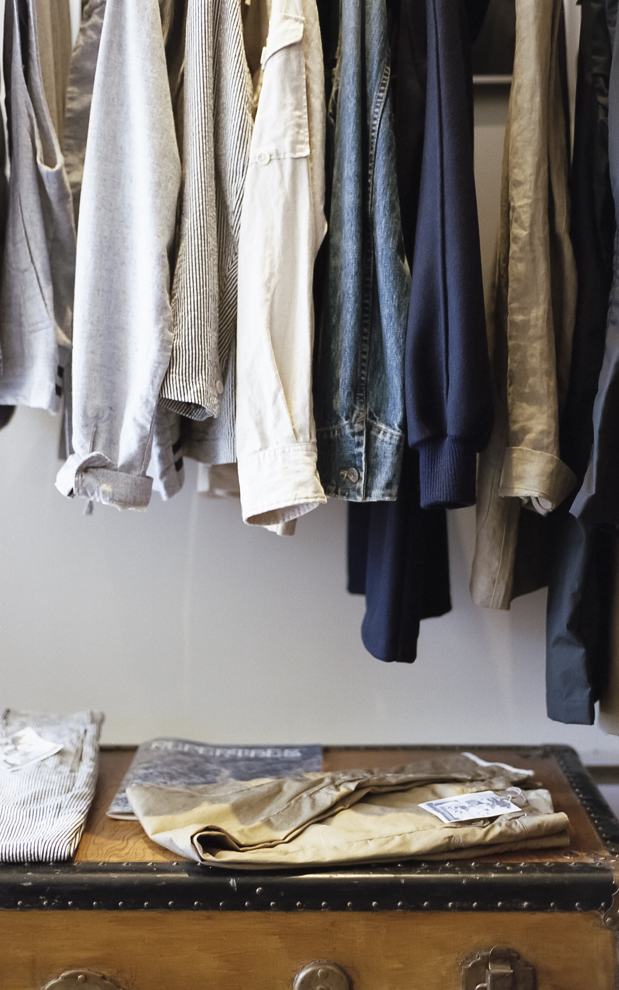 Shirts and jackets on hangers over a chest