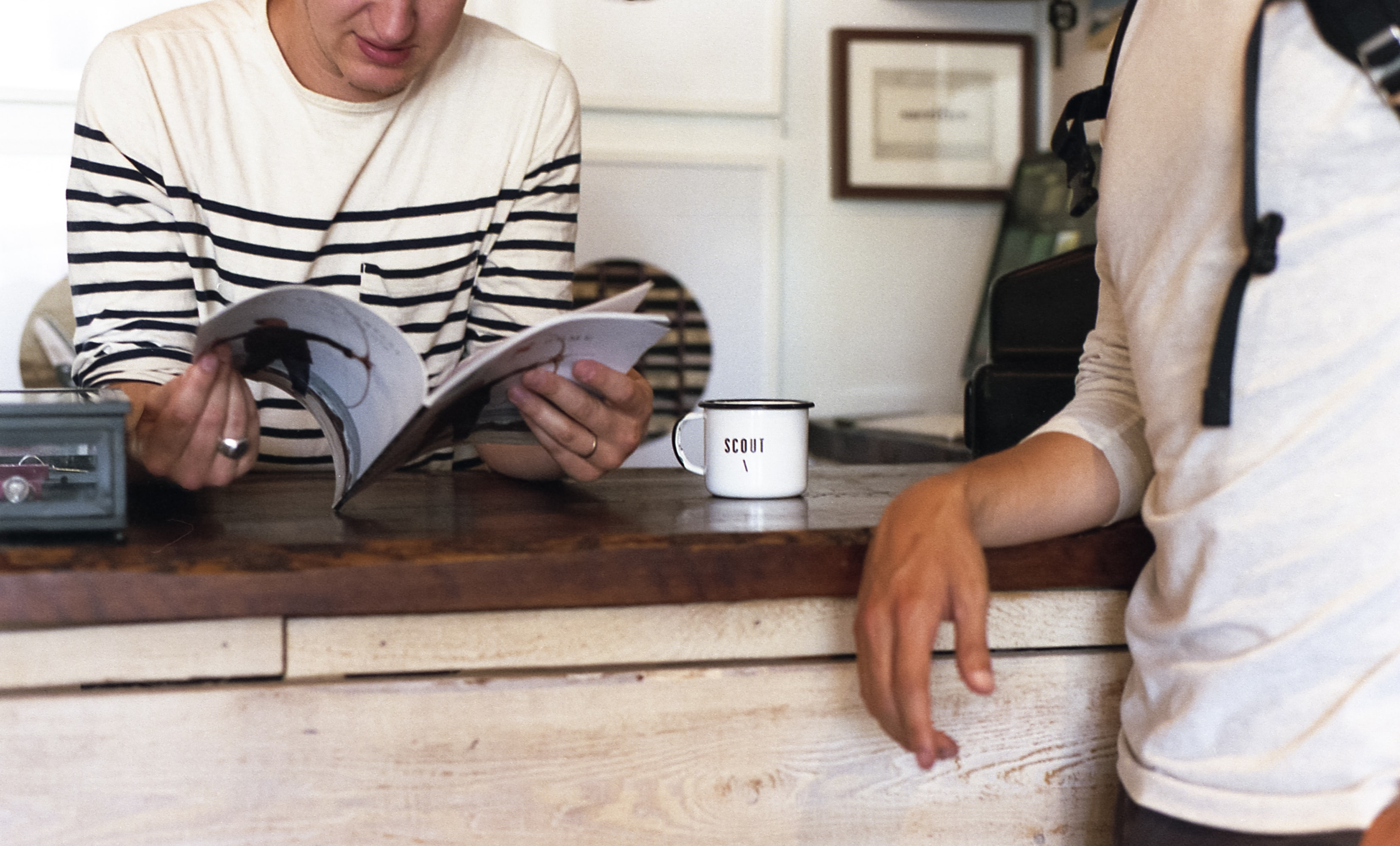 Two people standing near a counter with one of them reading a book