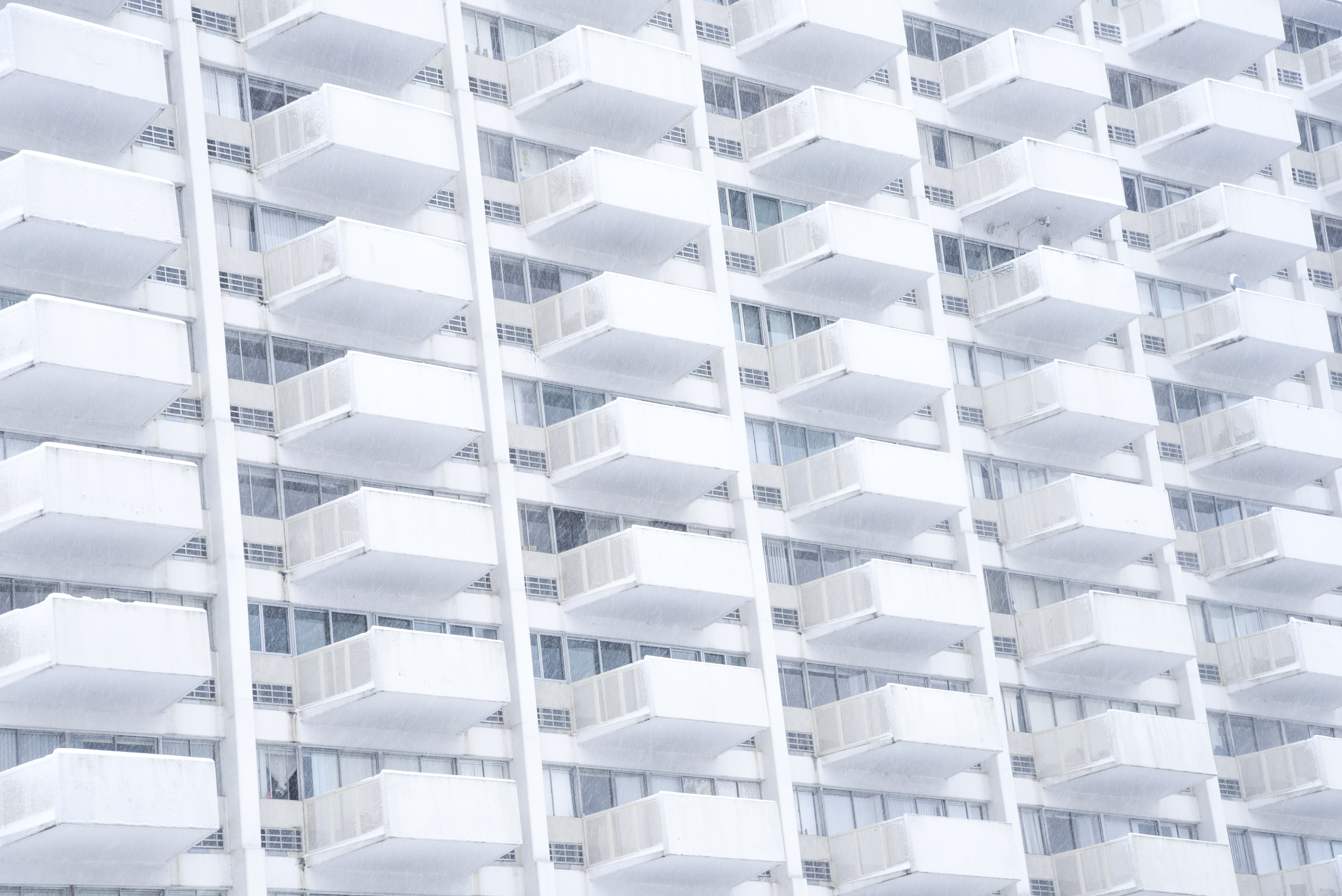 A stern white building facade with identical balconies