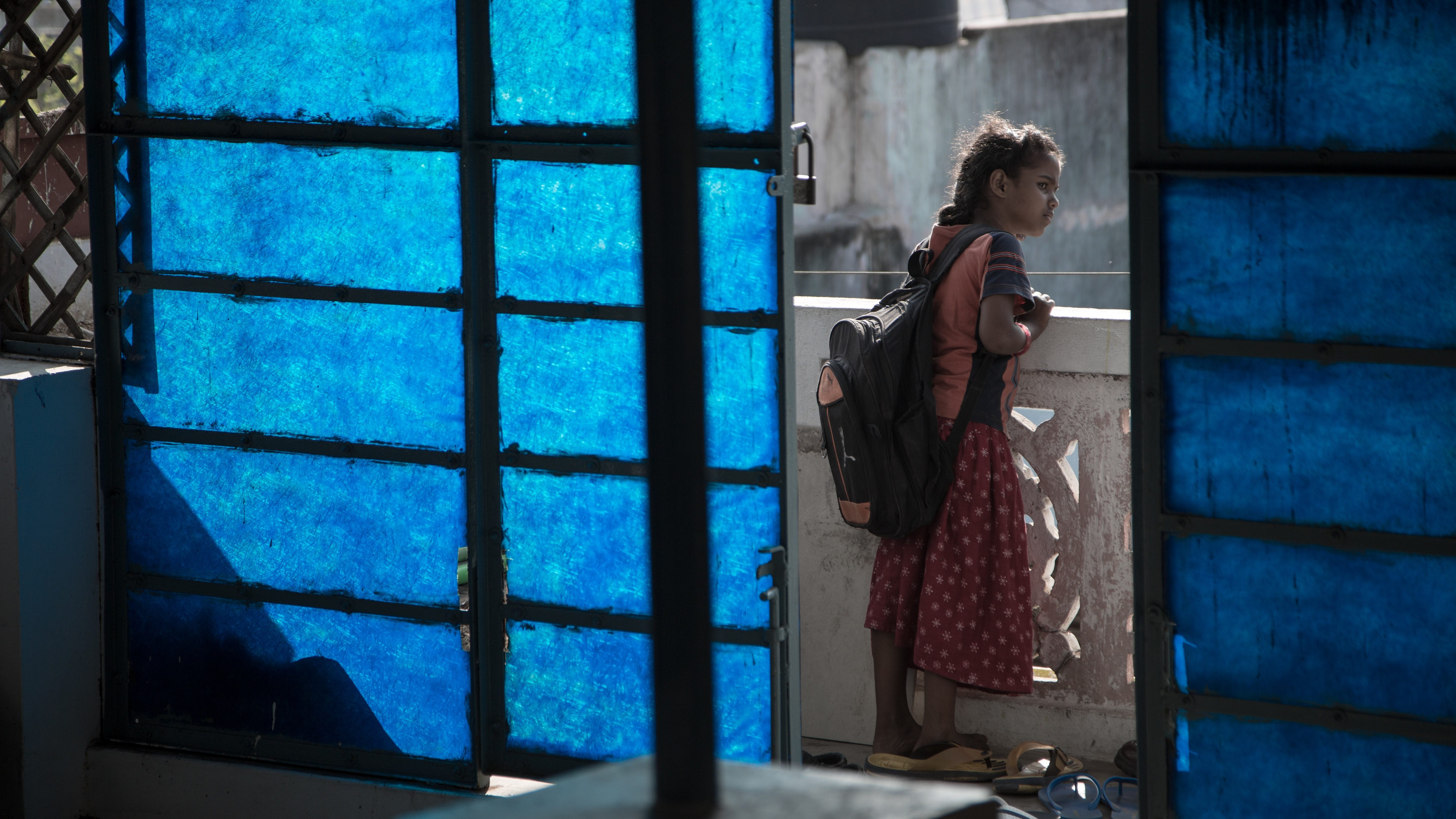 A girl, dressed for school, peers over the balcony outside of her home.
