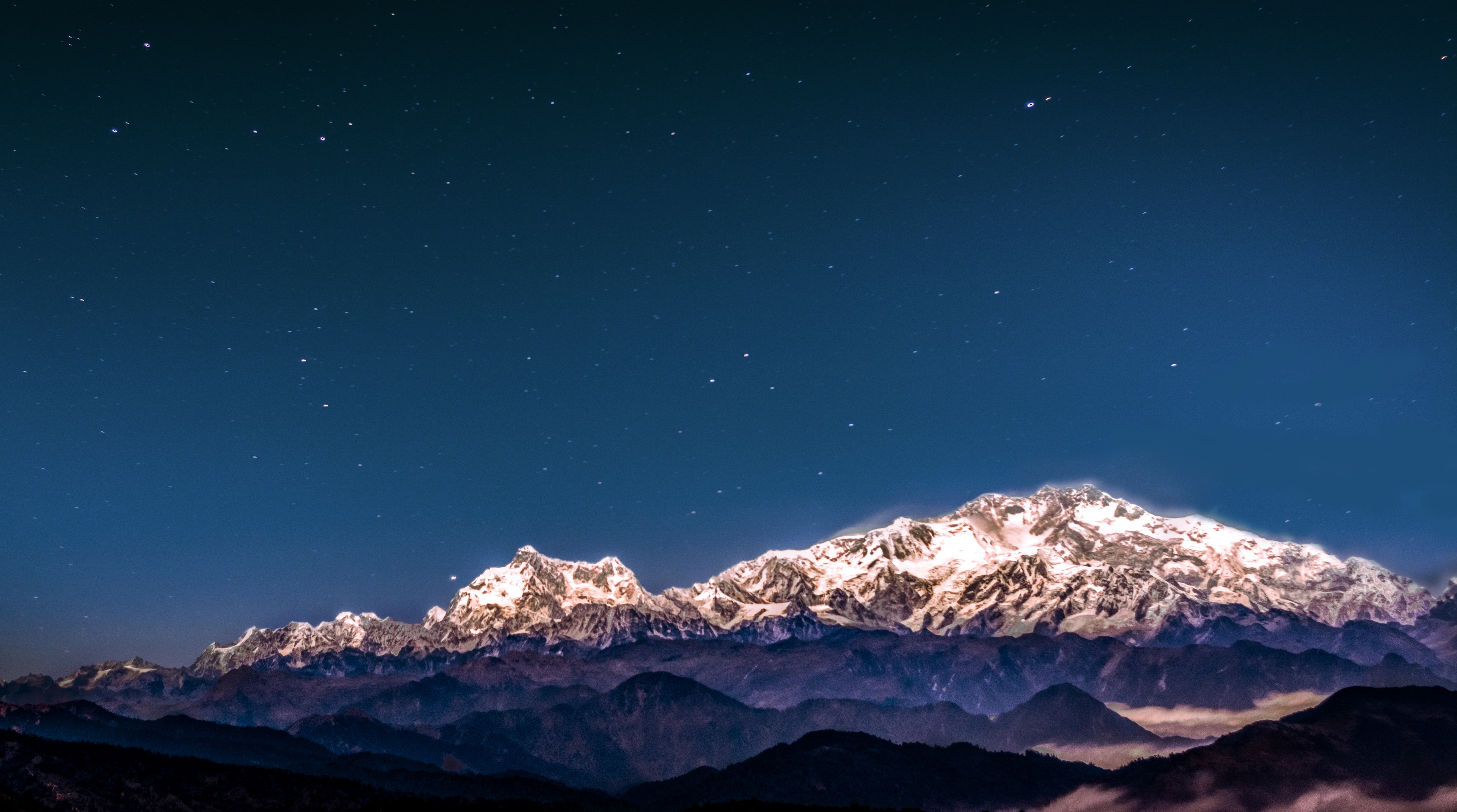 Snow covered mountains at Kanchenjunga South Peak during a starry night sky