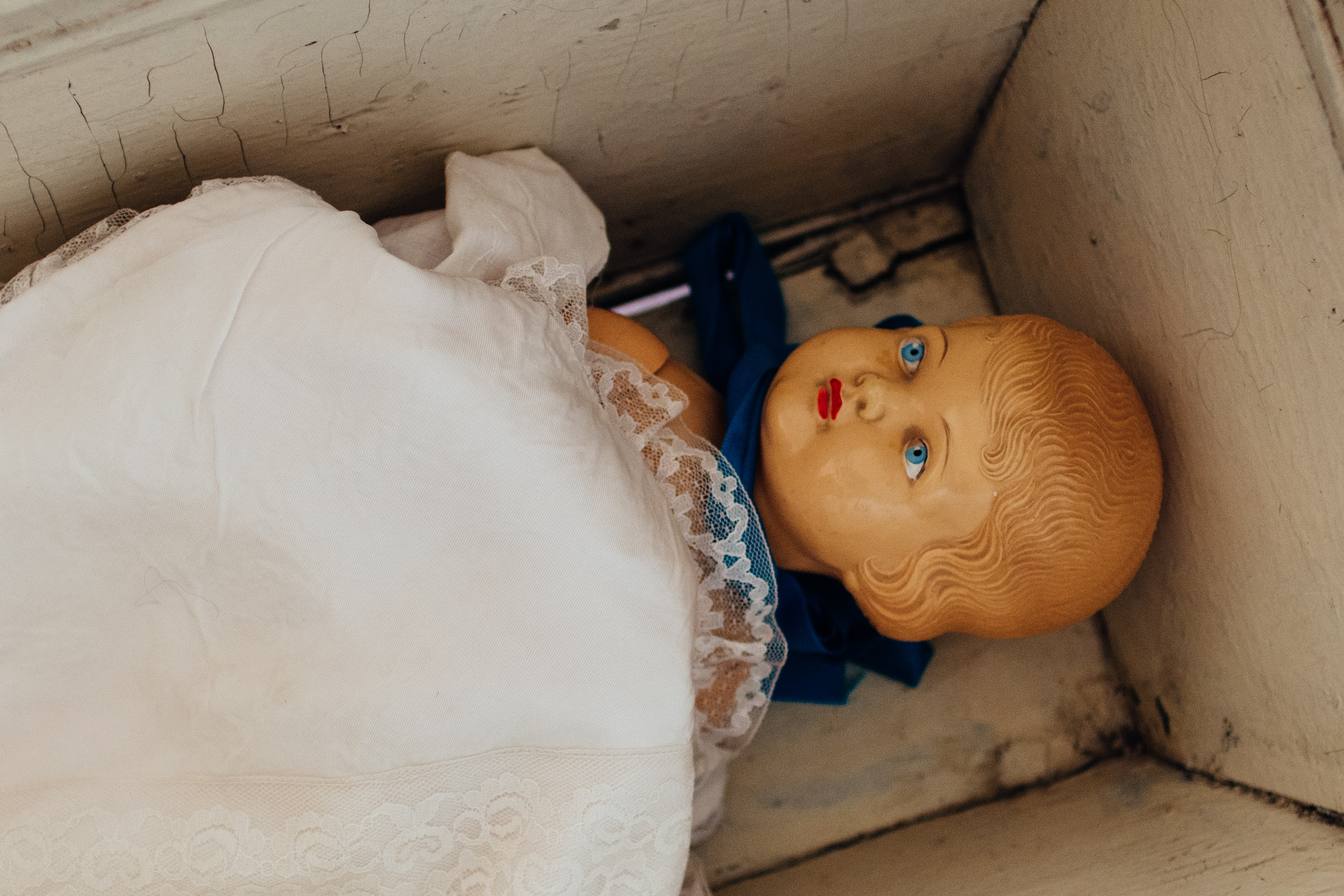 A baby doll in a cradle with a white lace over it