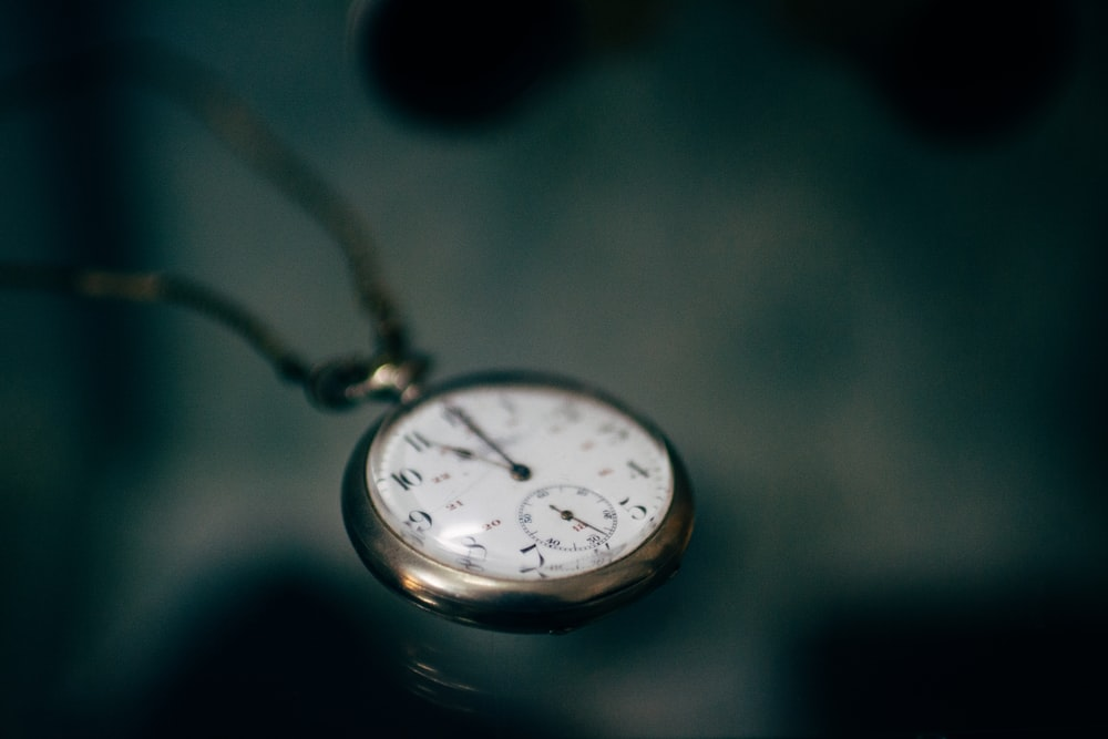 lowlight photography of white pocket watch
