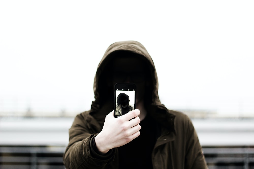 man wearing black hooded jacket and holding smartphone white taking close-up selfie