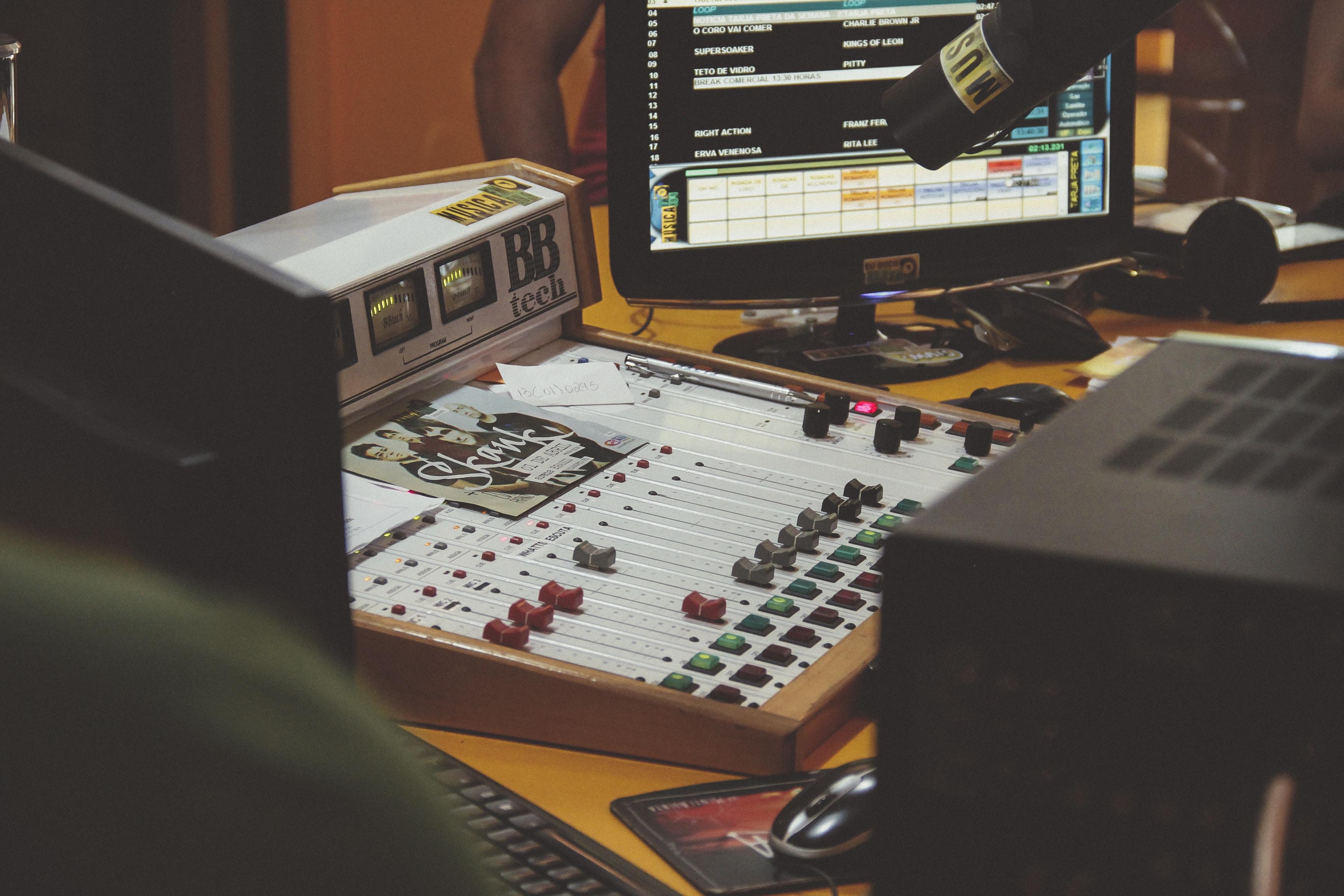 white audio mixer beside black flat screen computer monitor
