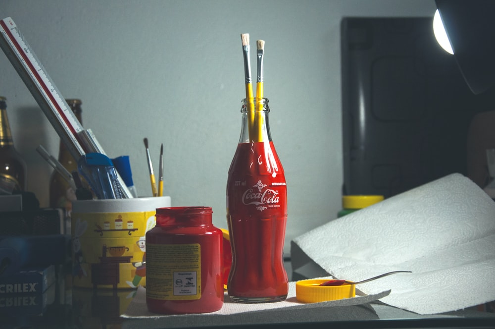 A Coca Cola Bottle Used As Beaker To Hold Paint Brushes With Other Beakers