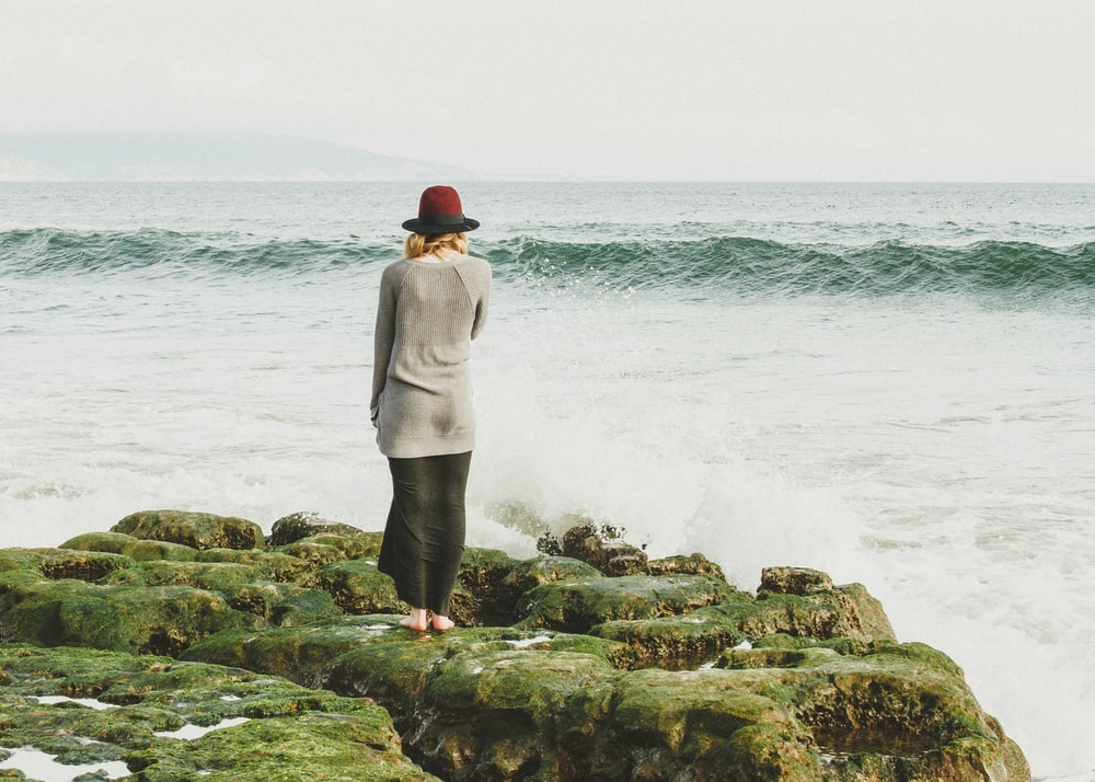 woman standing on green rocks near body of water with waves