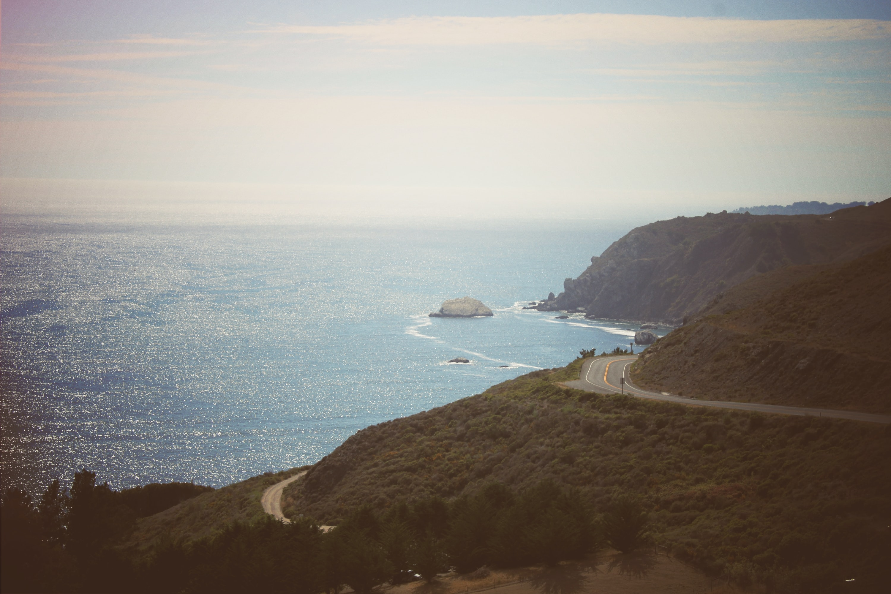 Drove view of a road winding around a mountain by the coast