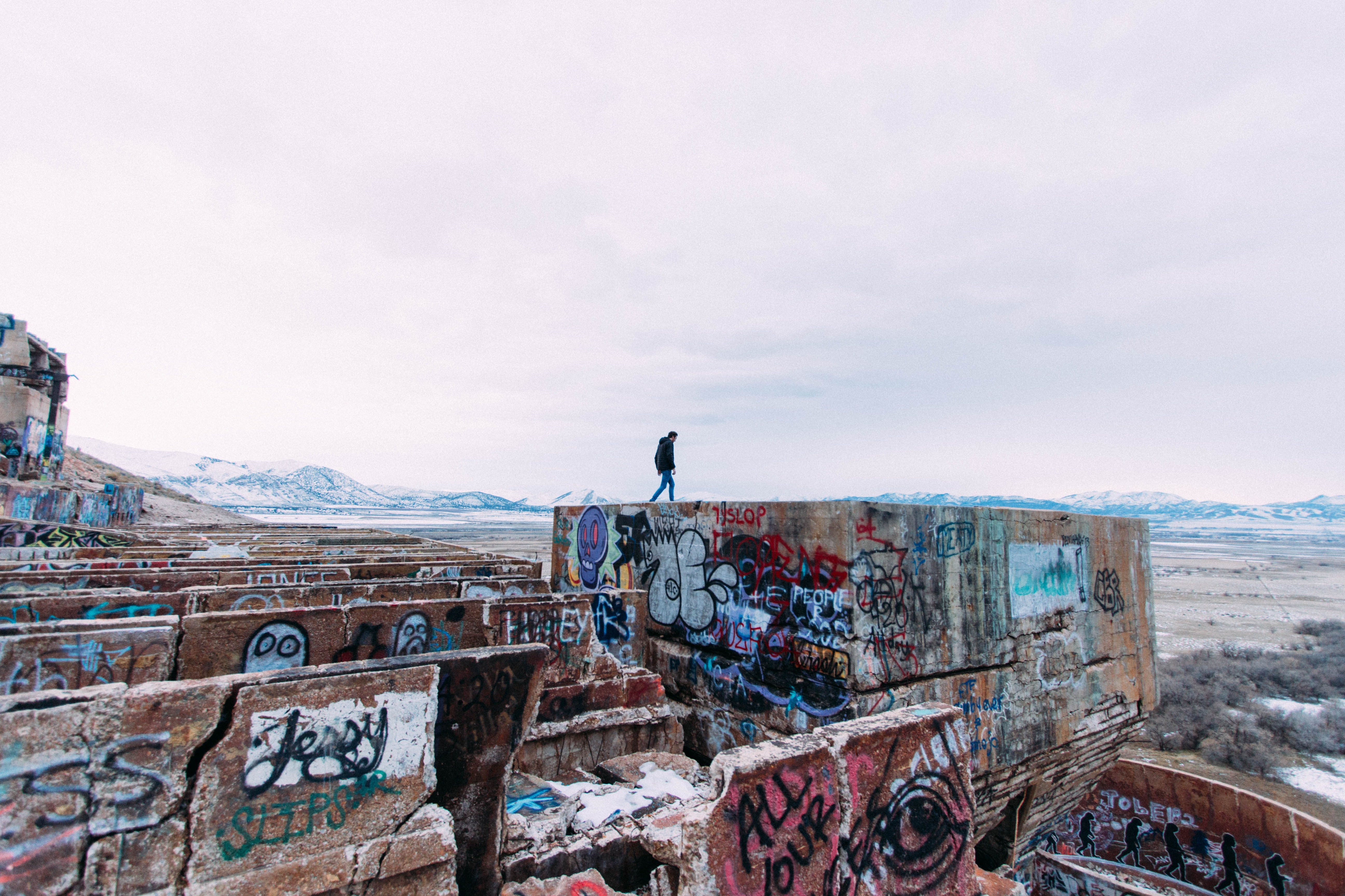 Person walking on concrete structure covered in graffiti in isolated region