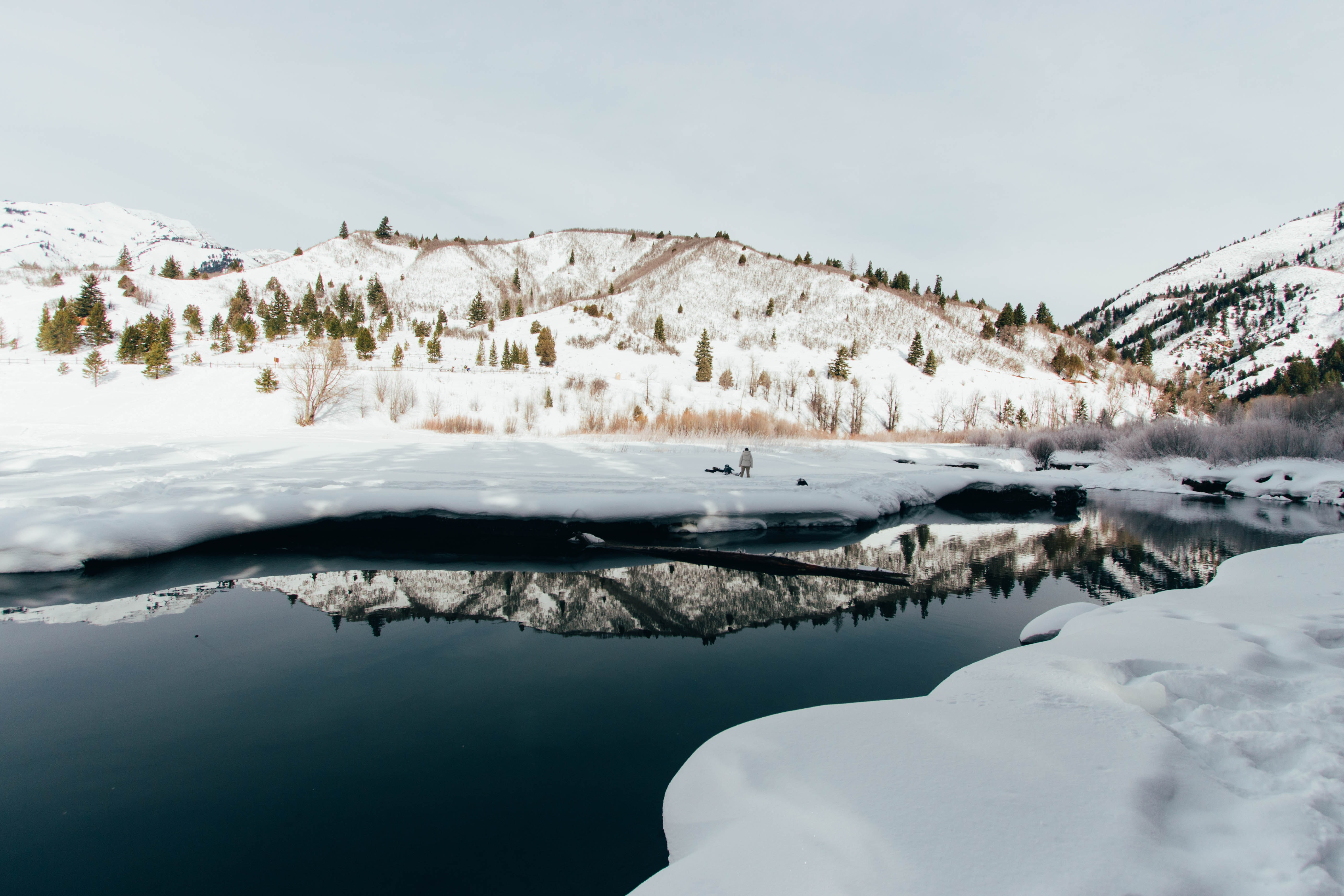 The reflections of a snow covered mountain  in a dark lake