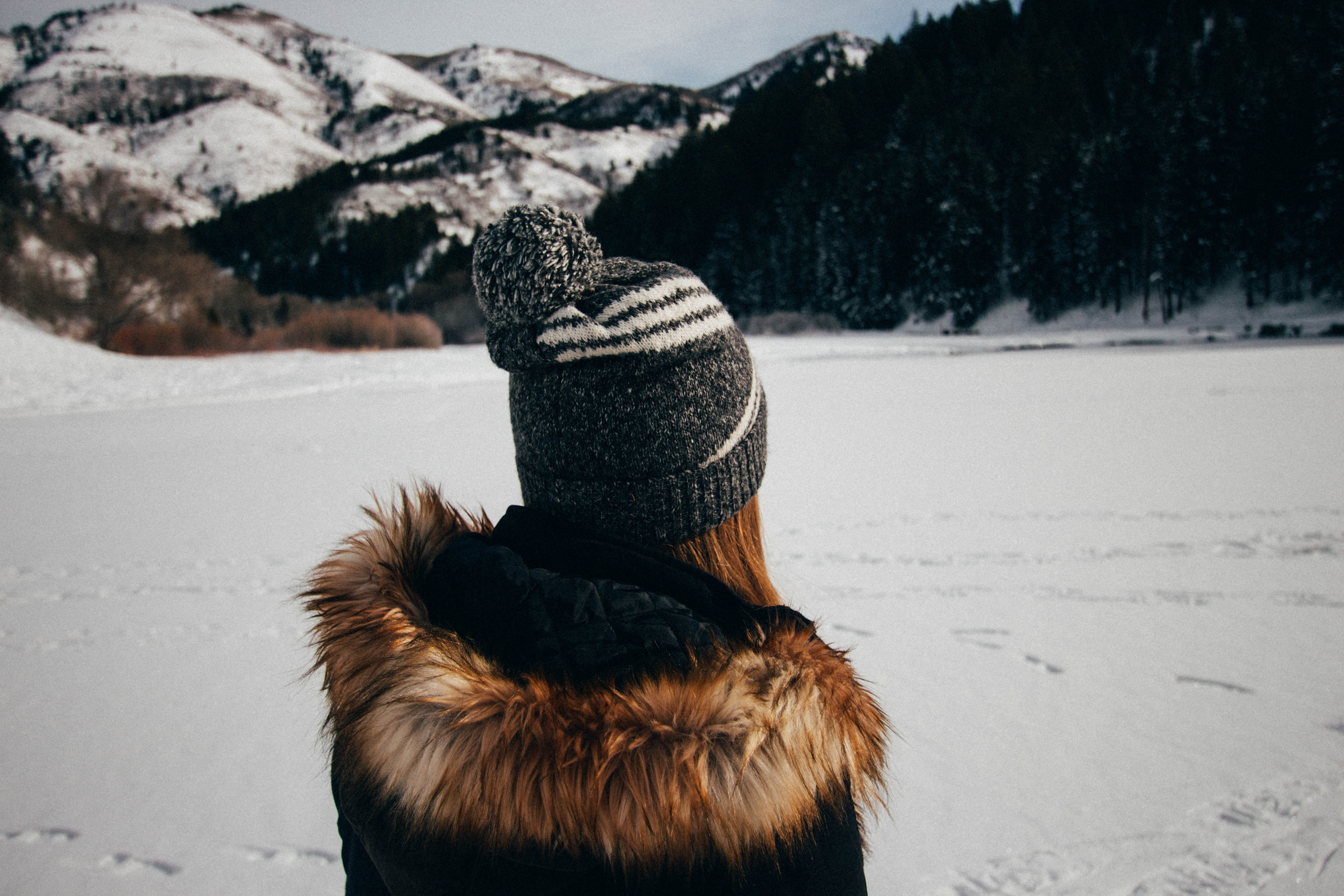 A woman in a fur coat and hat staring at a snow-covered mountain
