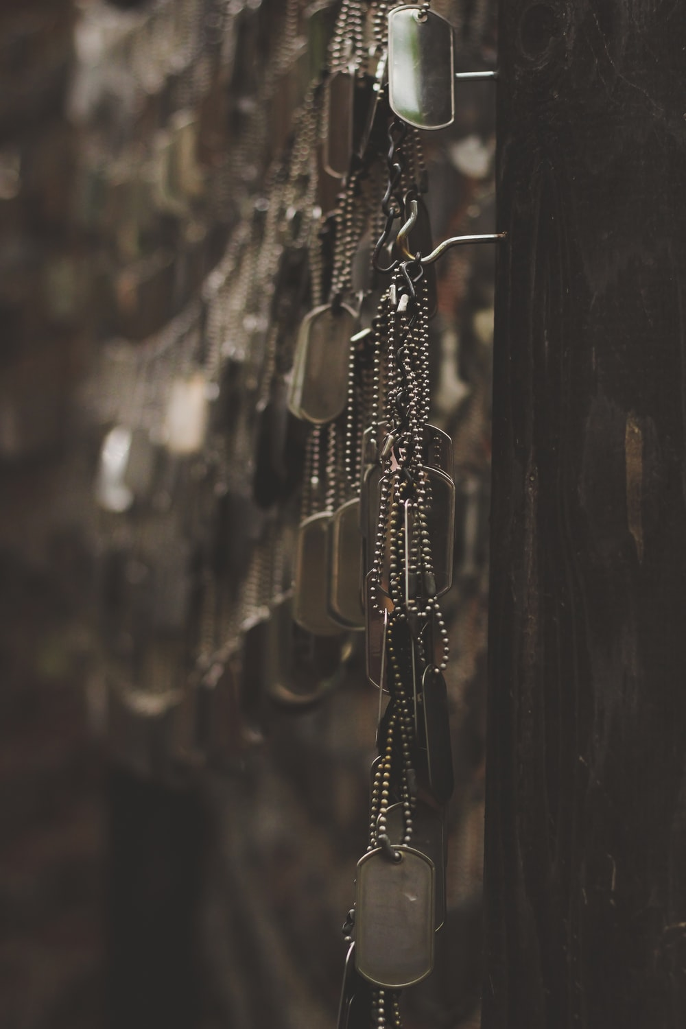 silver-colored god tags hanging on hooks shallow focus photography