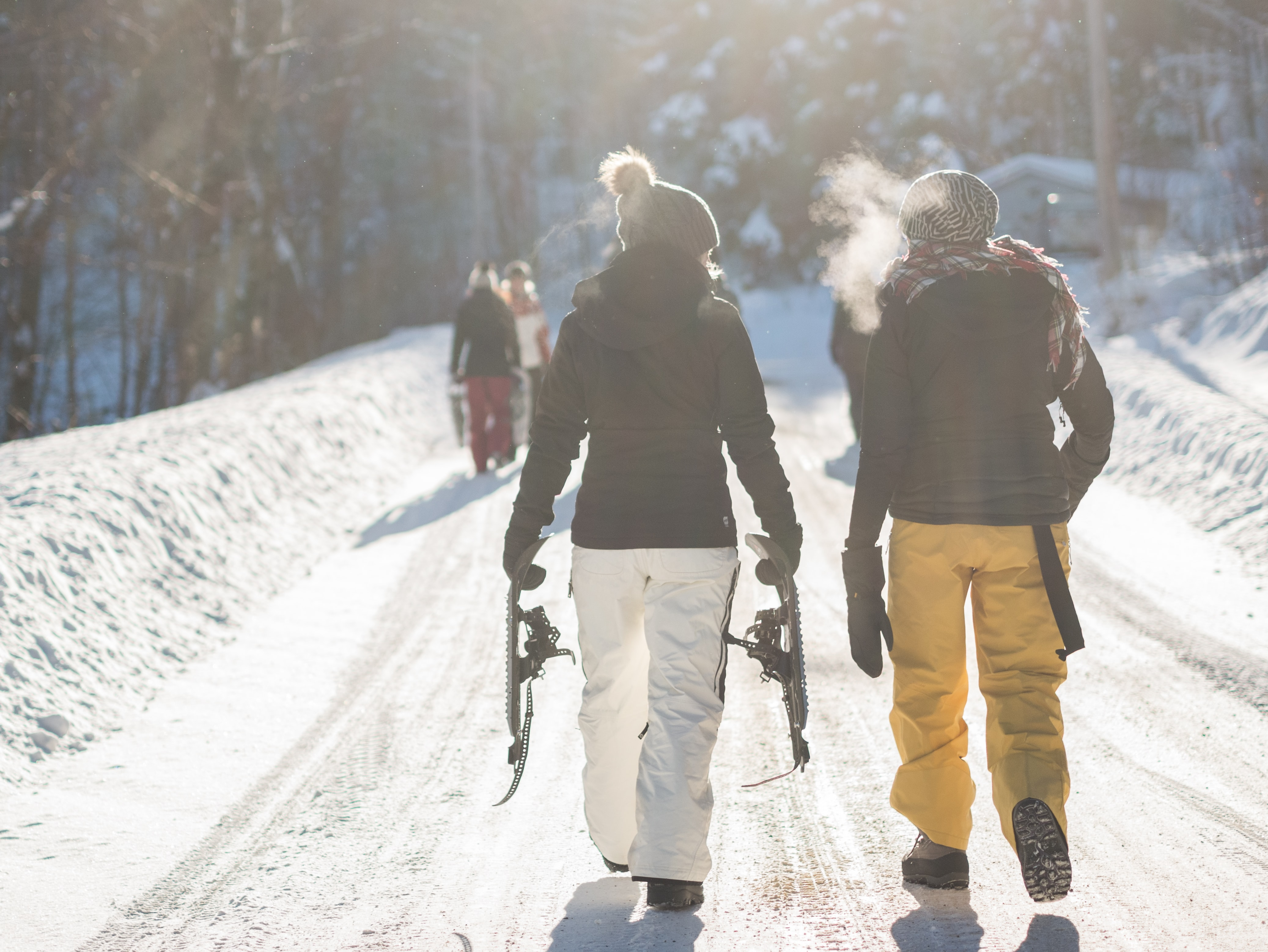 A few snowboarders walking a winter path with visible breath