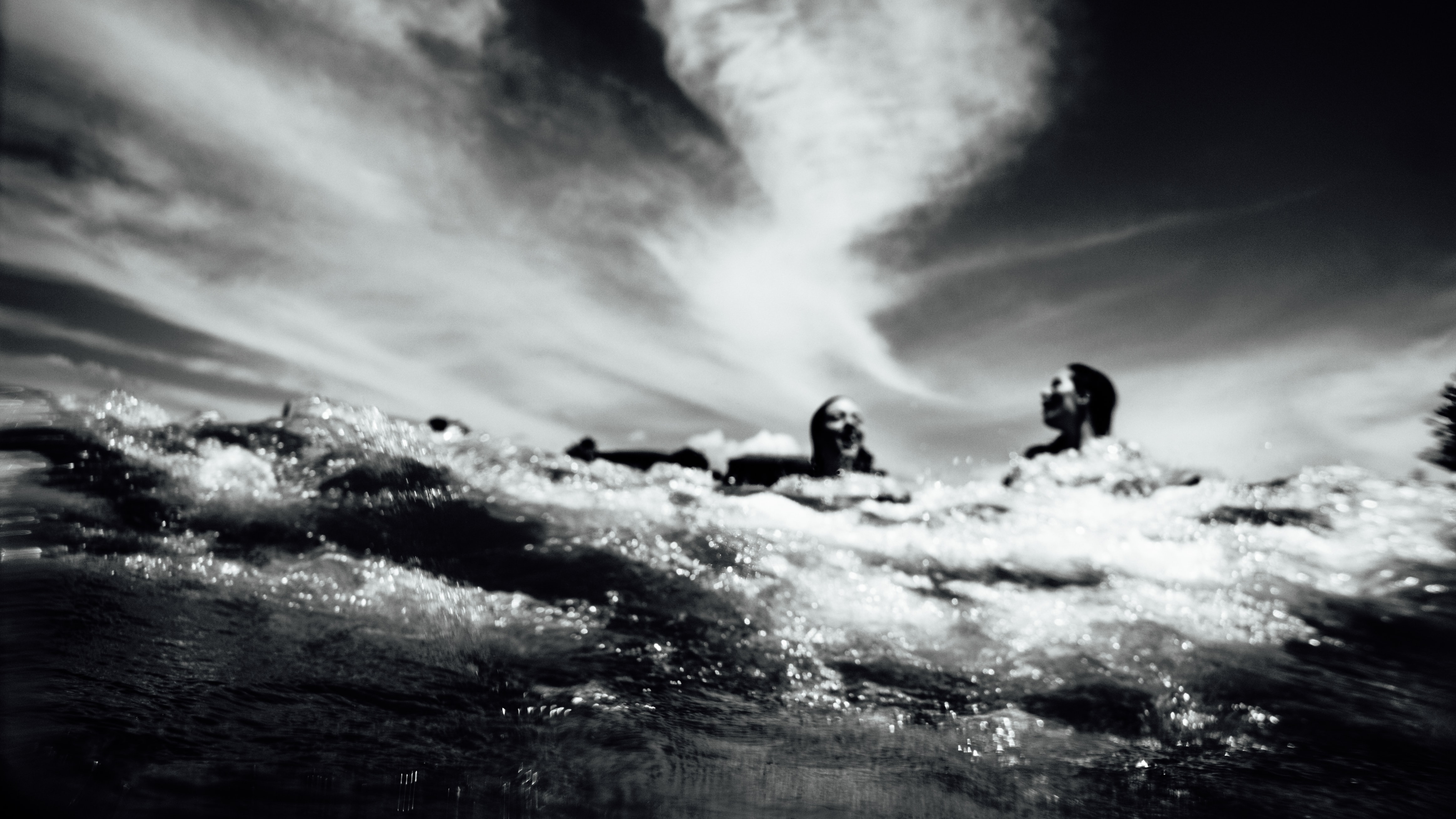 Black and white shot of people having fun in water with clouds in sky, Mount Maunganui