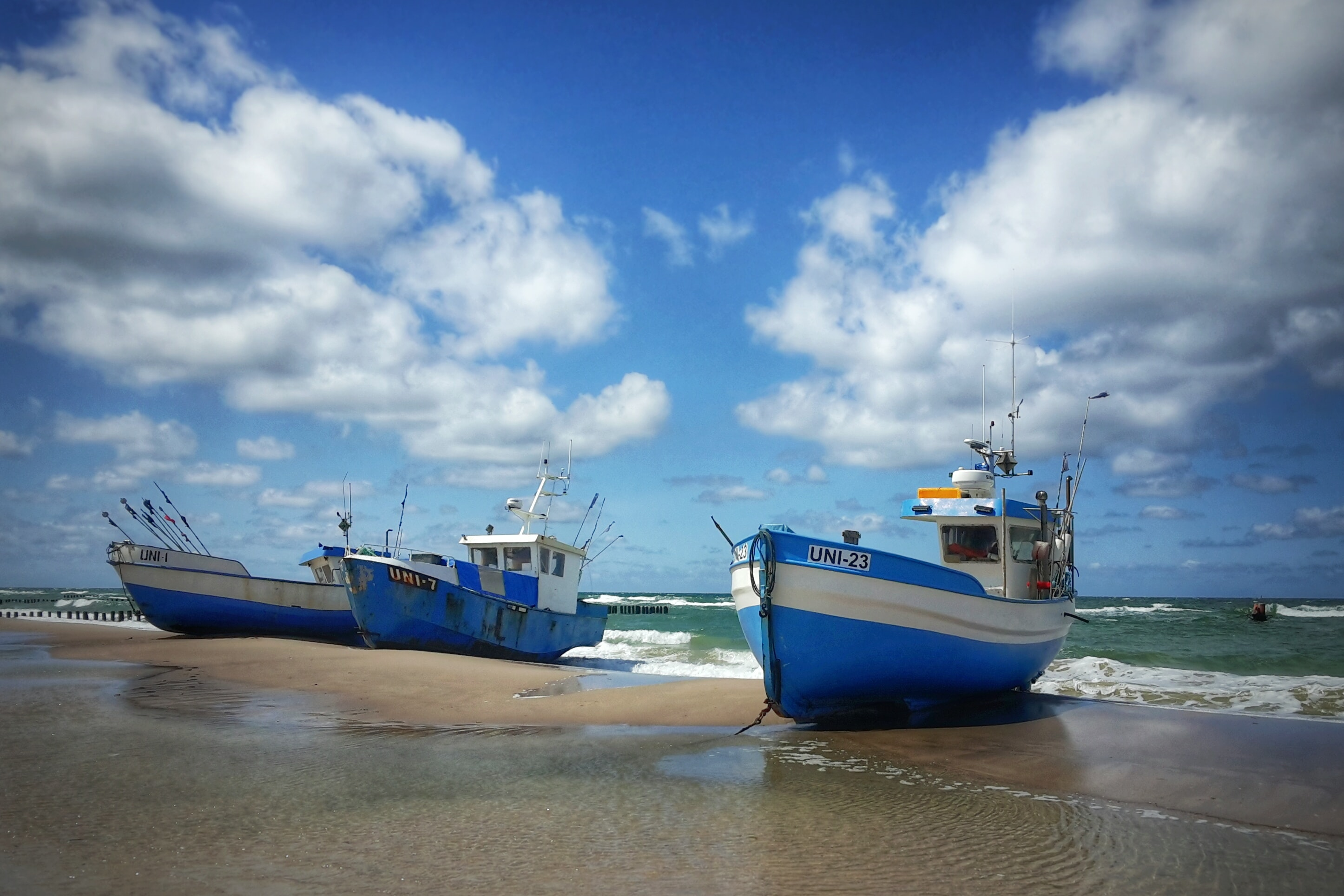 three blue boat docked on seashore during daytime