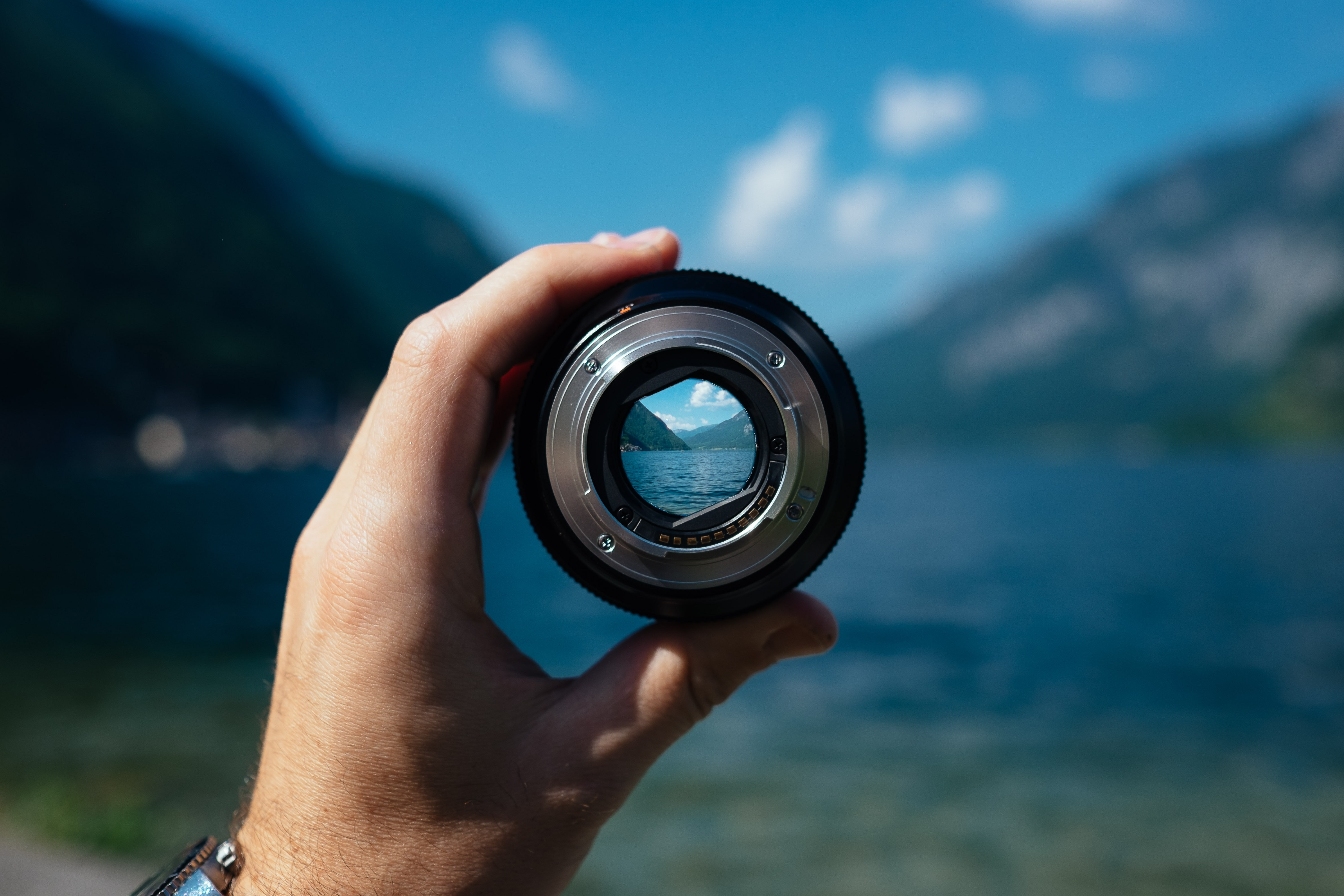 A person's hand holding a camera lens over a mountain lake