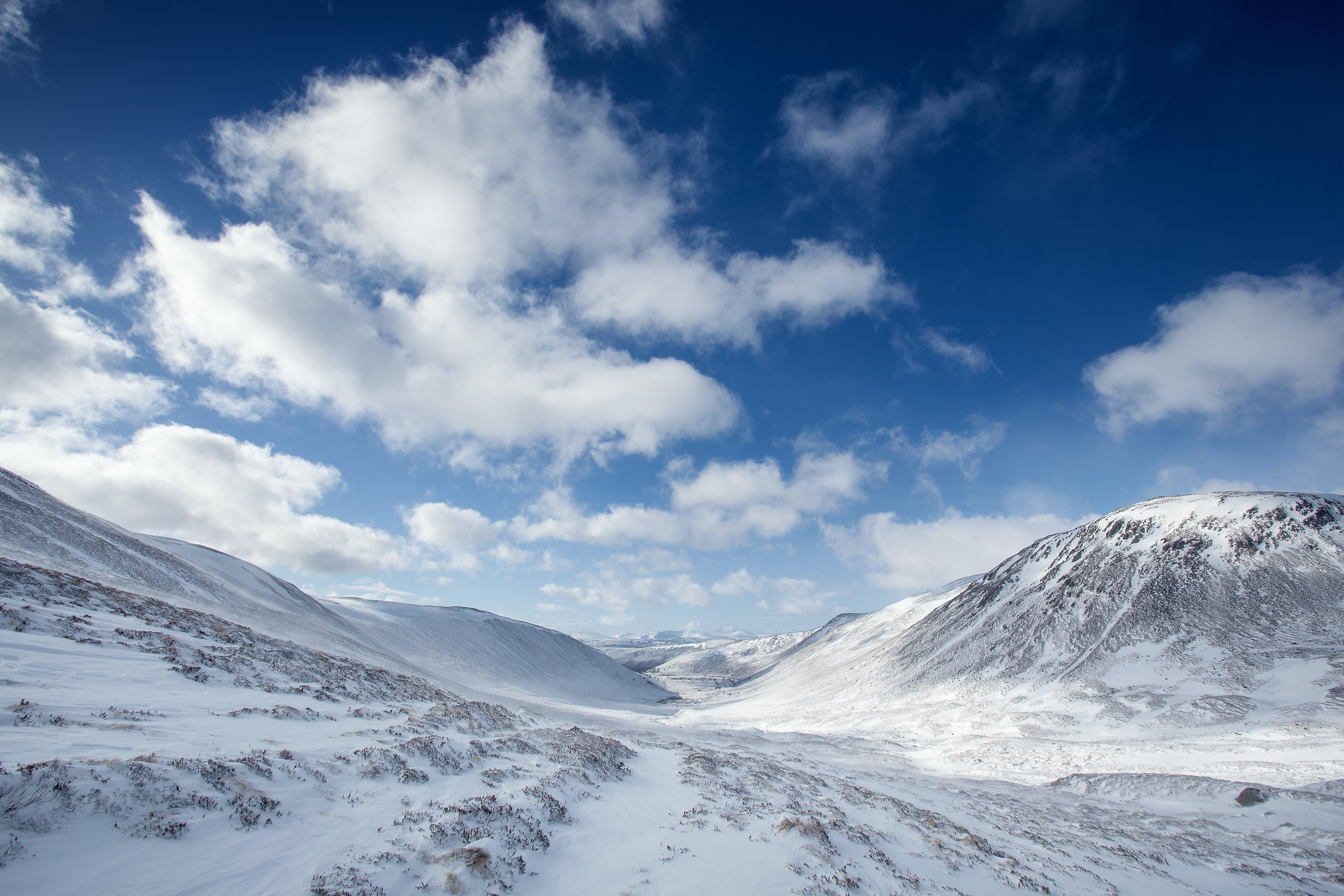 A snow filled valley in between mountains and a cloudy, blue sky in Cairngorms National Park in Scotland