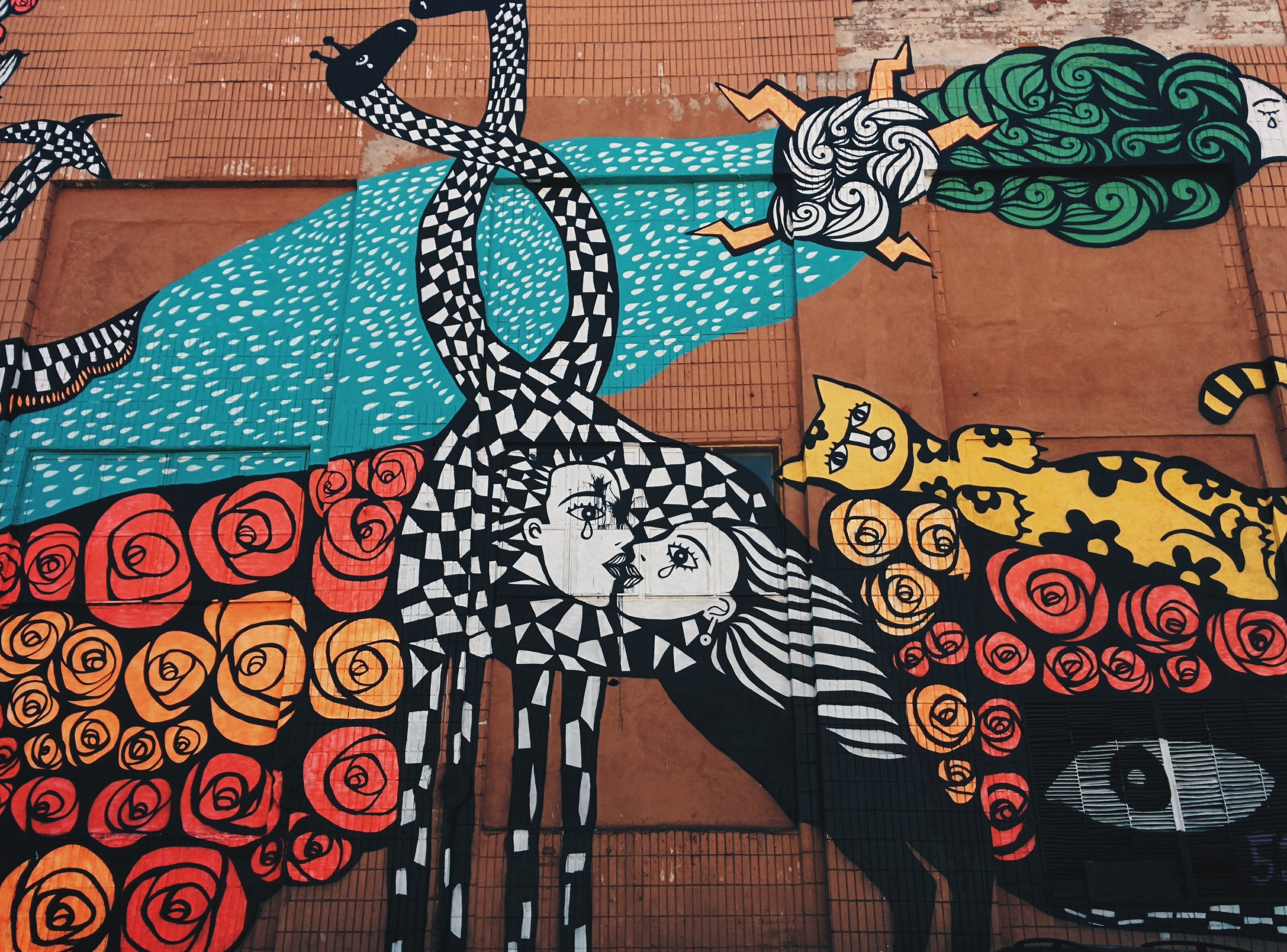 A wall painting of black and white checkered distorted man and woman kissing, surrounded by flowers, a yellow cat, the sun and more.