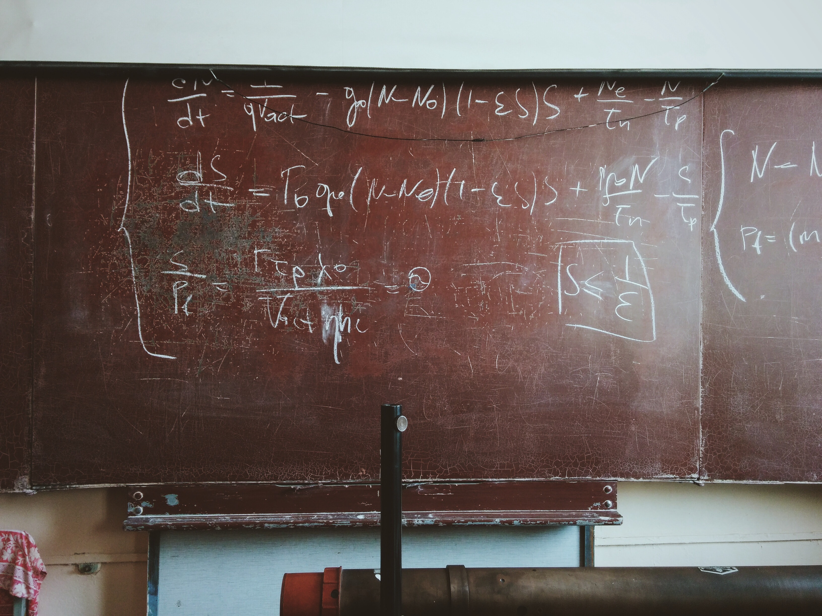 Equations written in chalk on a worn-out blackboard