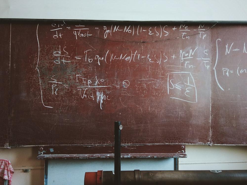 Equations written in chalk on a worn-out blackboard