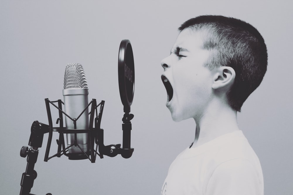 boy singing on microphone with pop filter