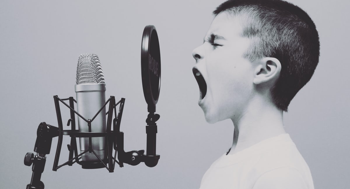 A young boy screaming into a microphone.