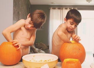 two boys holding pumpkins on table inside house
