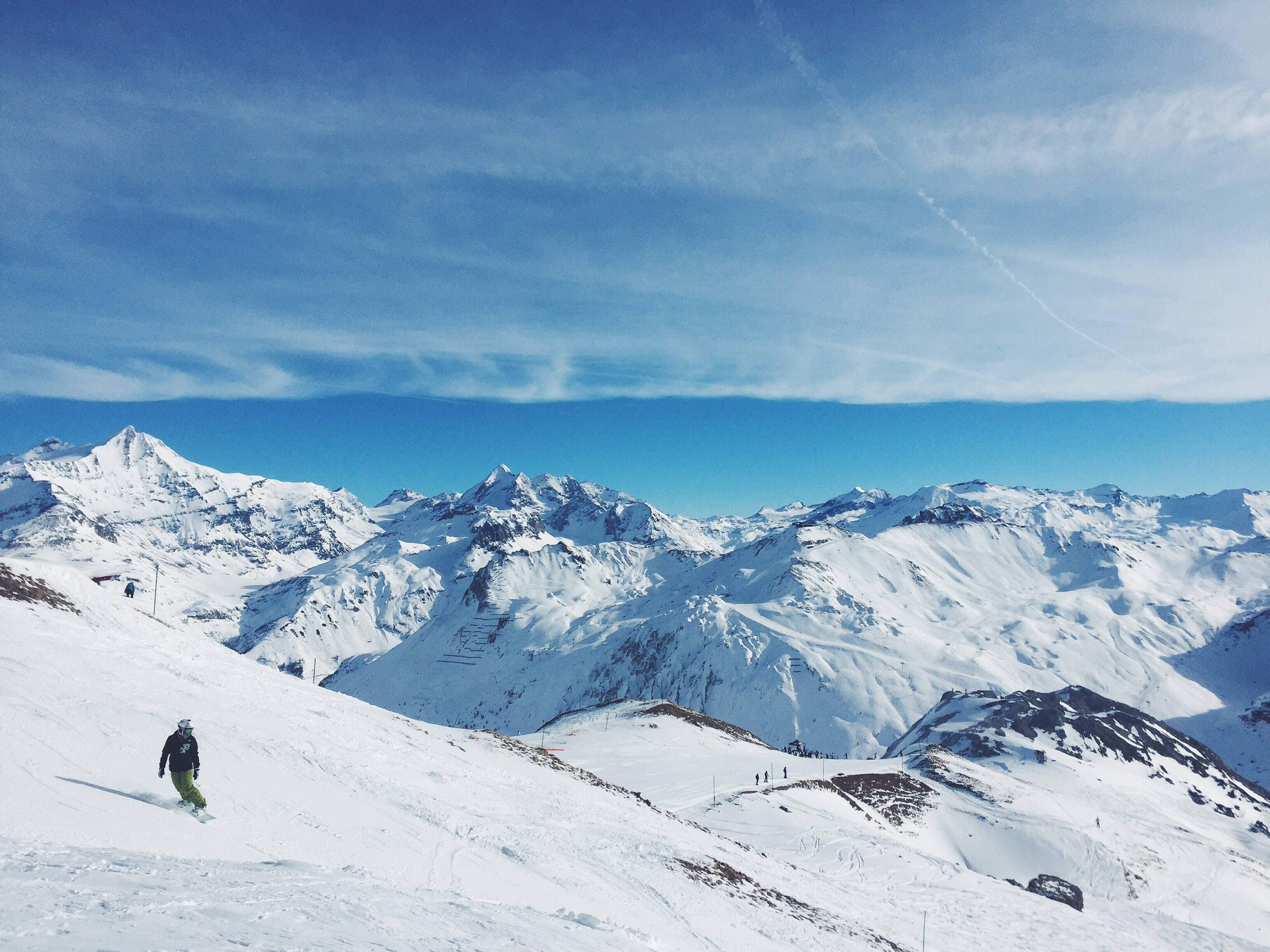 Snowboarder on top of snowcapped mountains high up in the sky