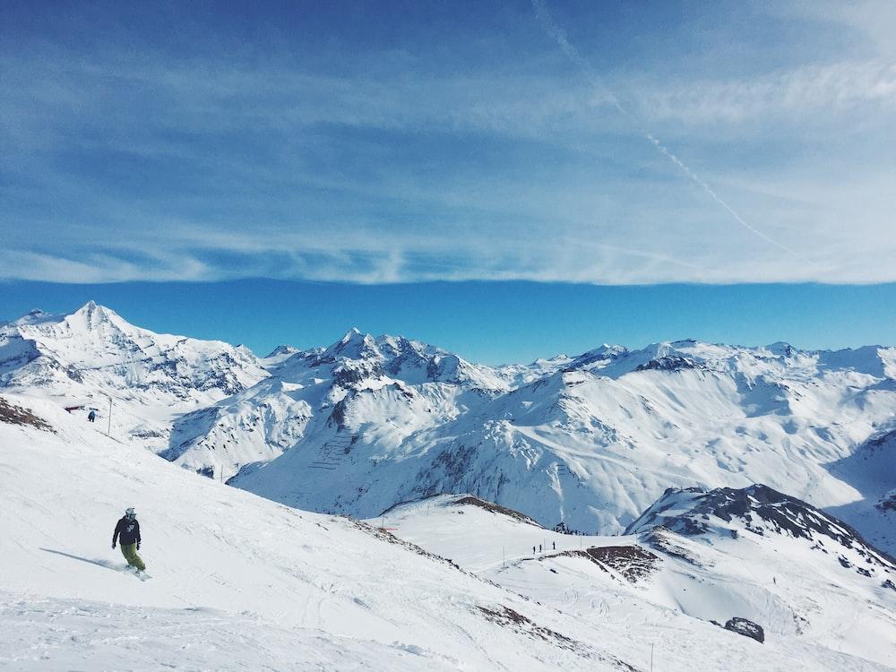 man snowboarding on mountain under cloudy sky