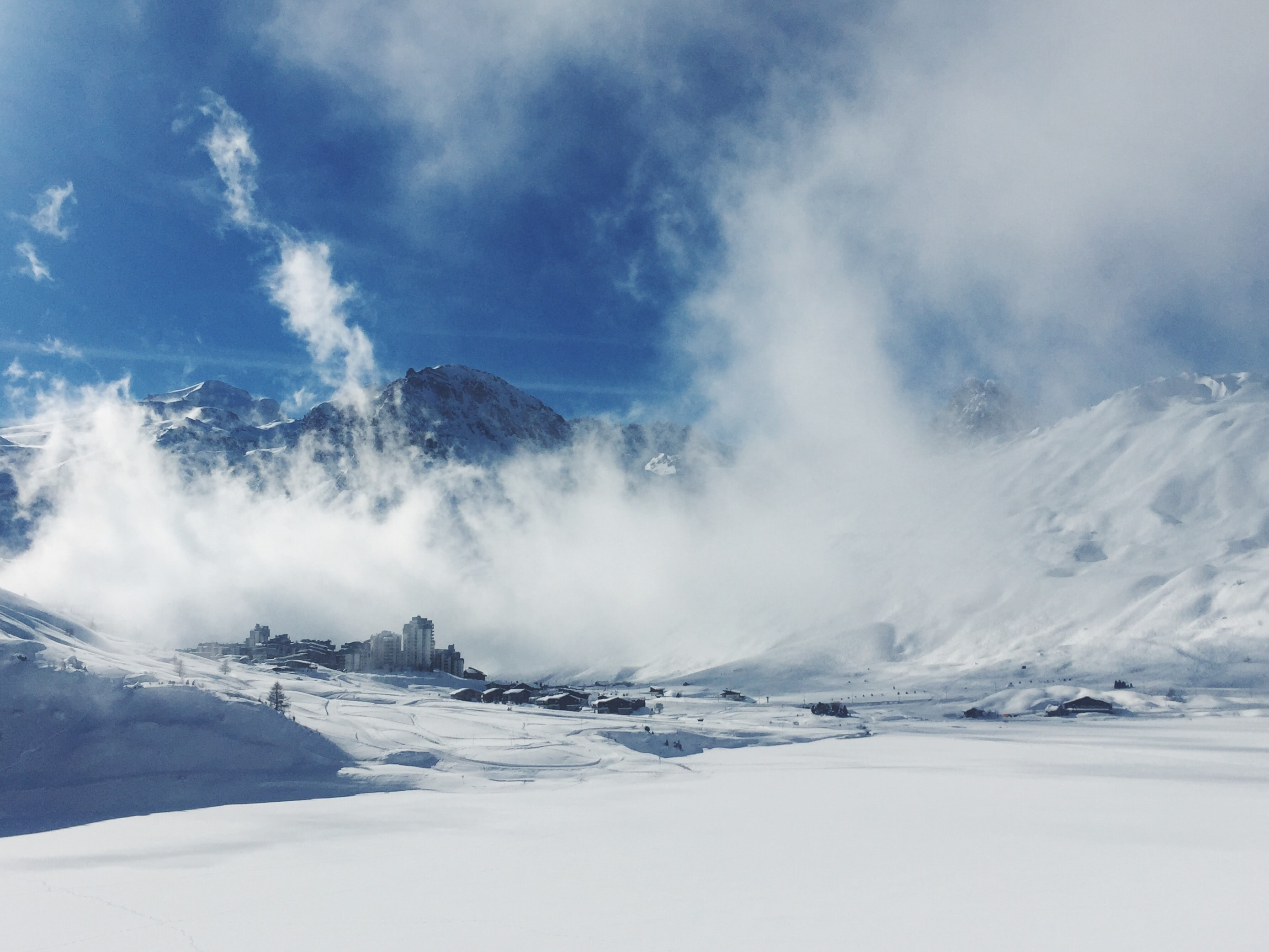 snow-covered mountain under blue cloudy sky