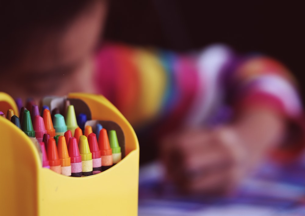 selective focal photo of crayons in yellow box