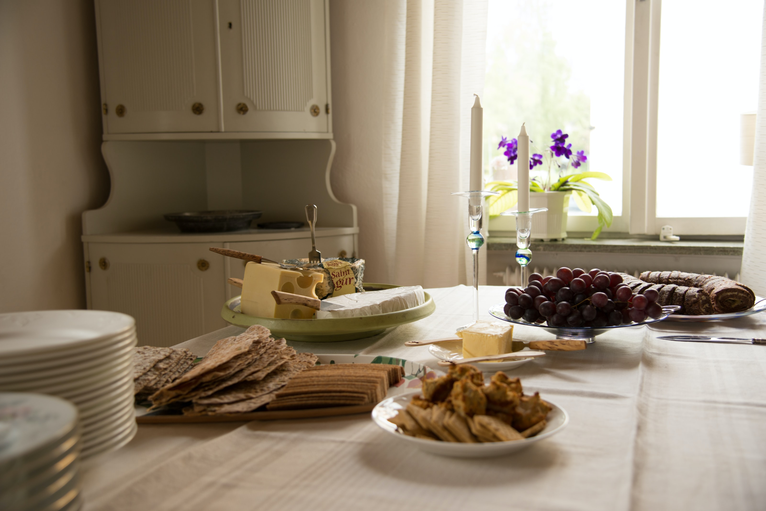 Charcuterie spread with grapes, bread, crackers, and cheese
