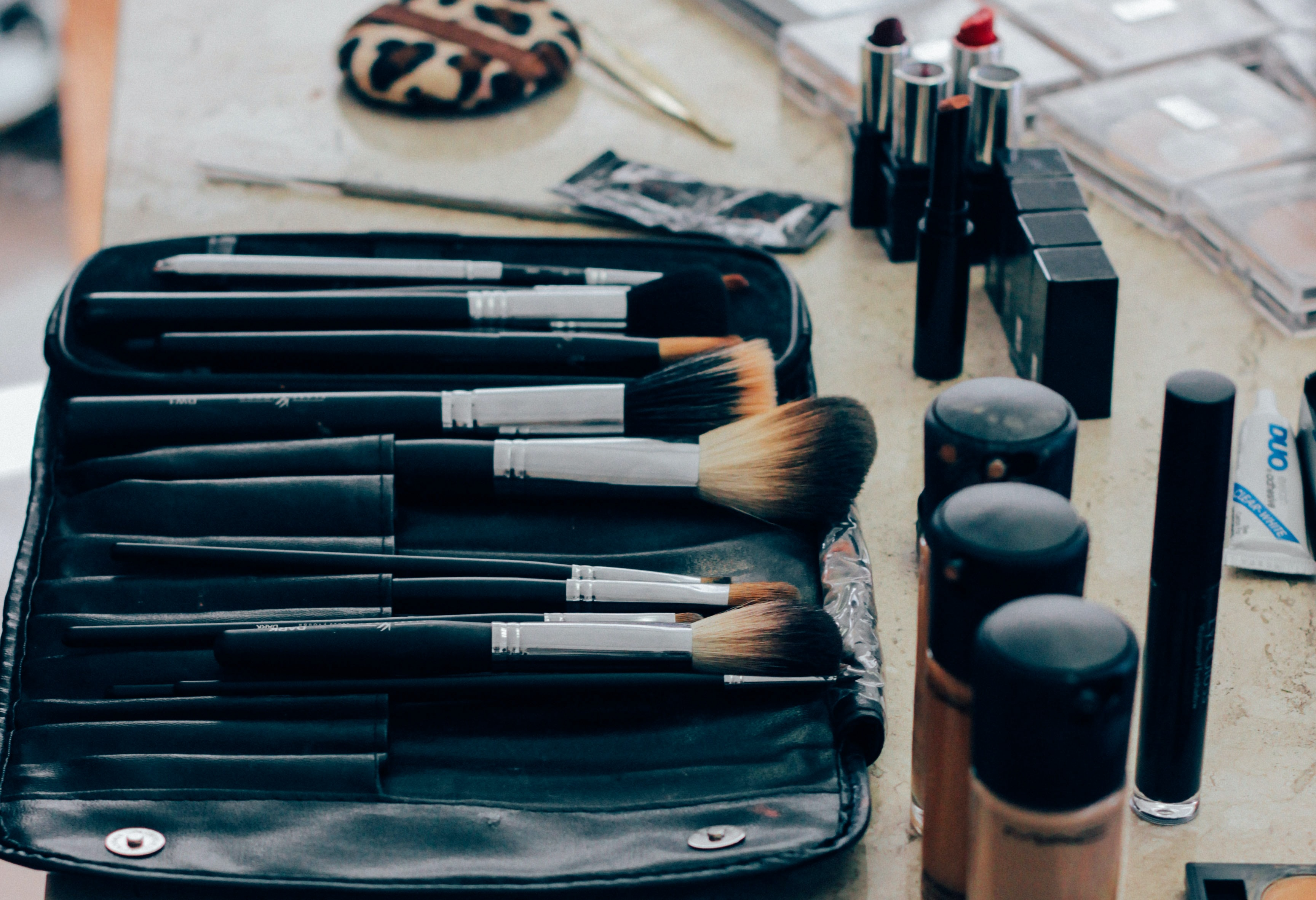 Make-up brushes and various cosmetics on a table