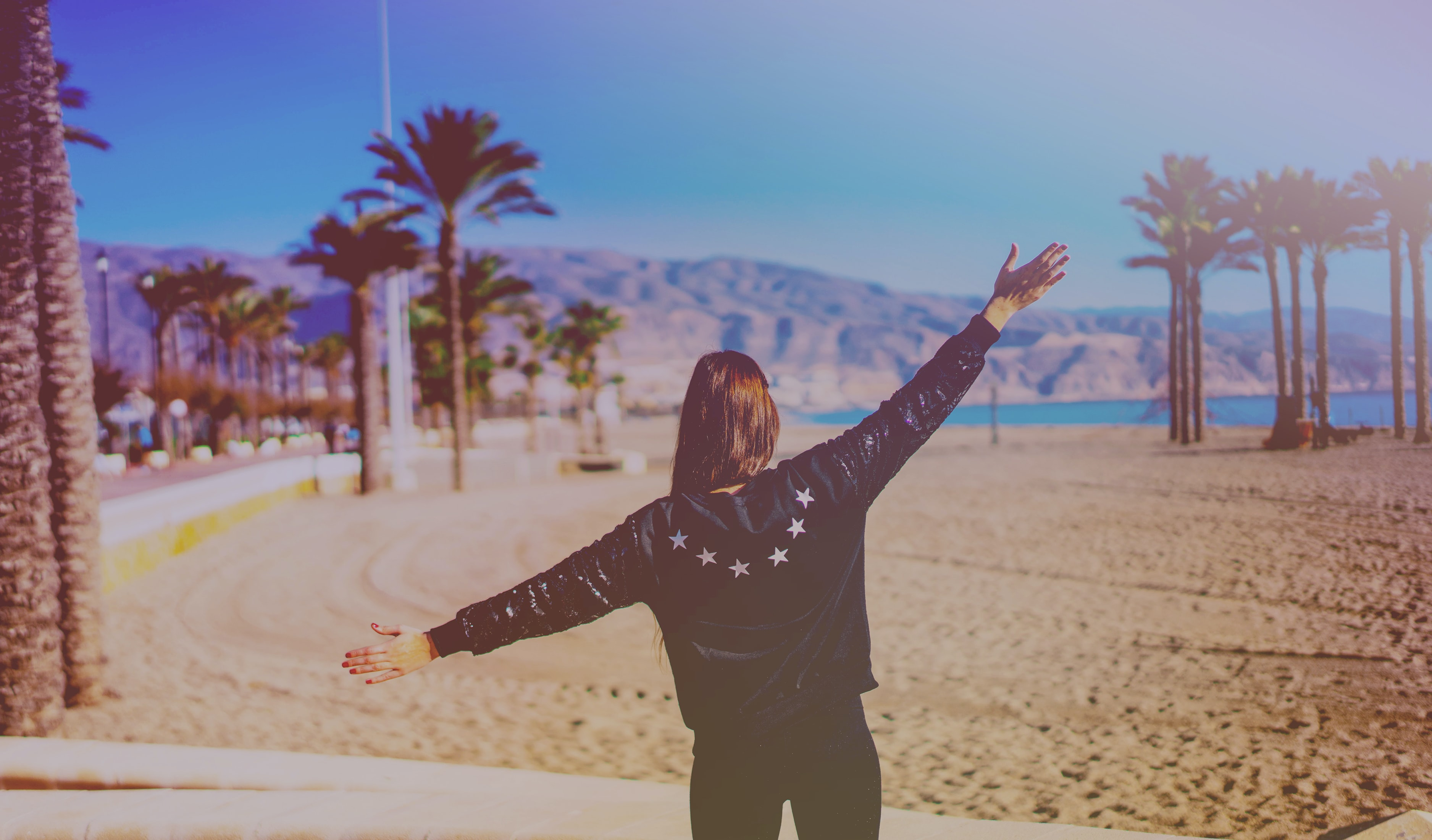 Woman in a jacket spreads her arms on the beach at Roquetas de Mar