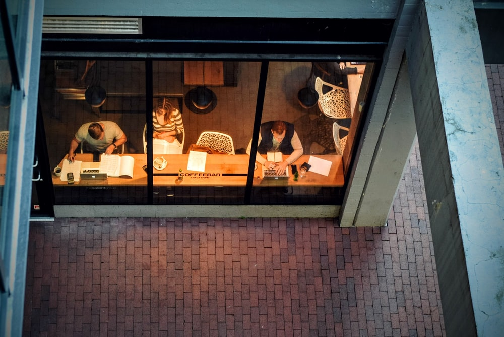 People working at their laptops in a coffee shop seen through the window