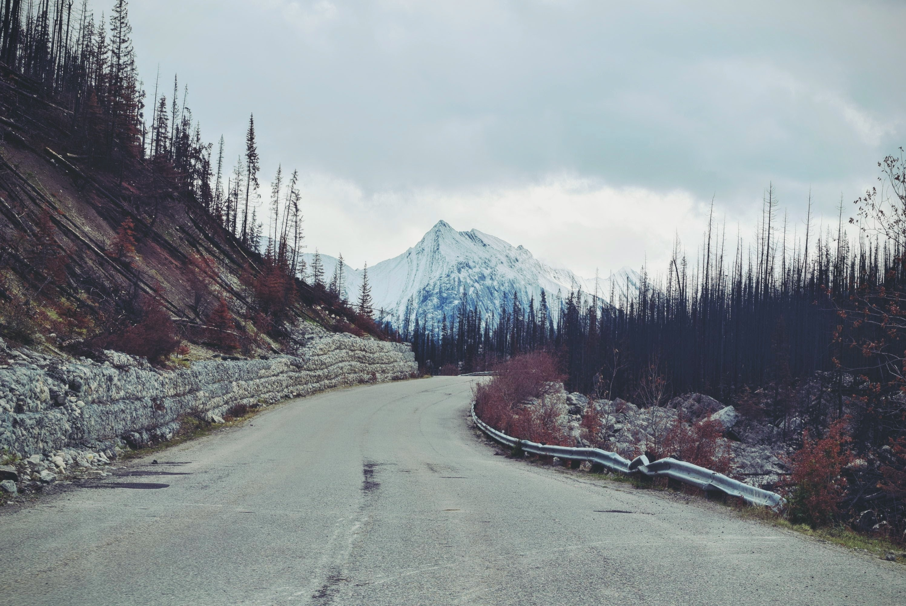 gray asphalt road towards snow covered mountain during daytime