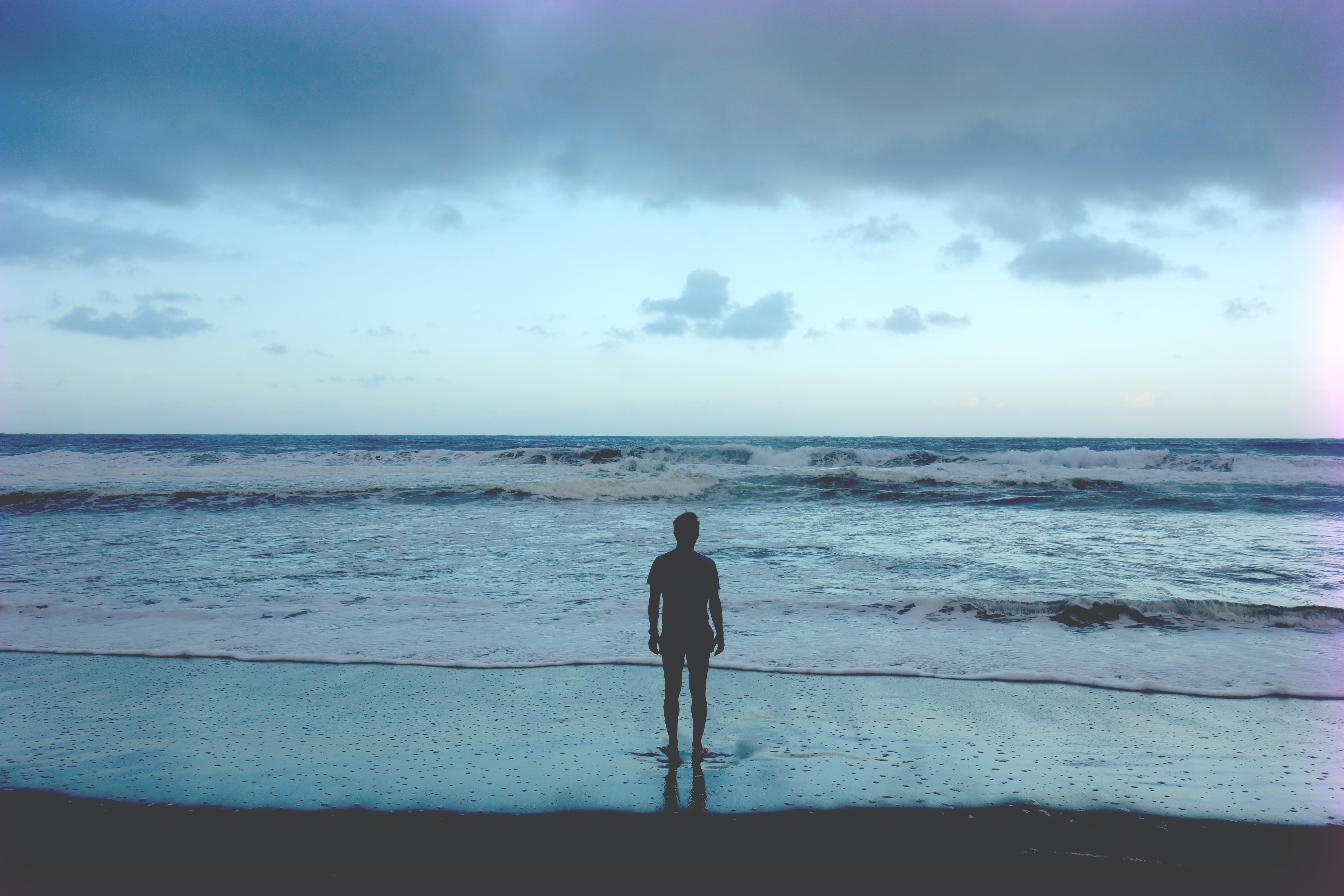 Man silhouette standing on the beach looking at the ocean in Waipio Valley