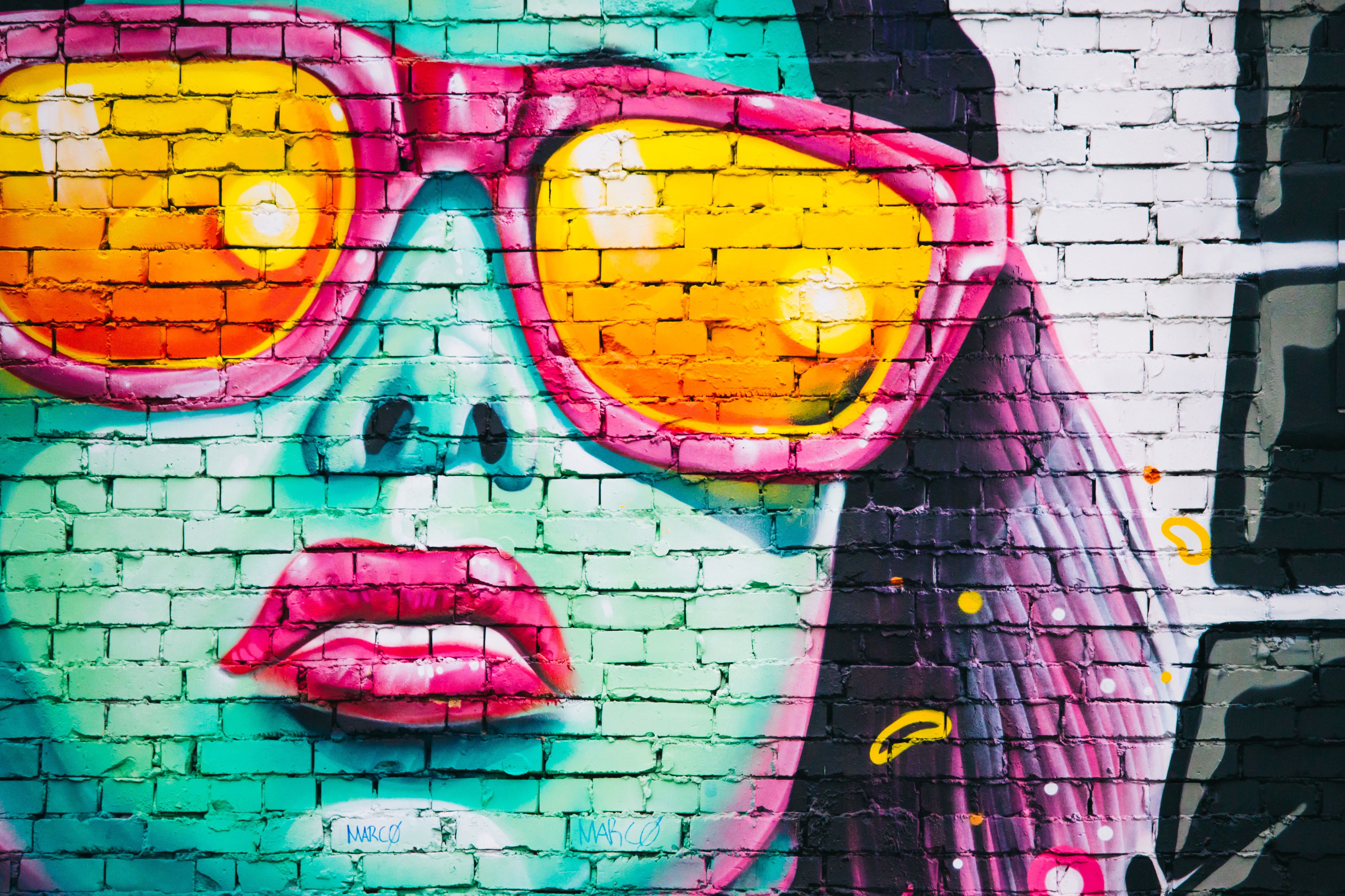 Neon mural of woman wearing sunglasses and pink lipstick on brick wall in England