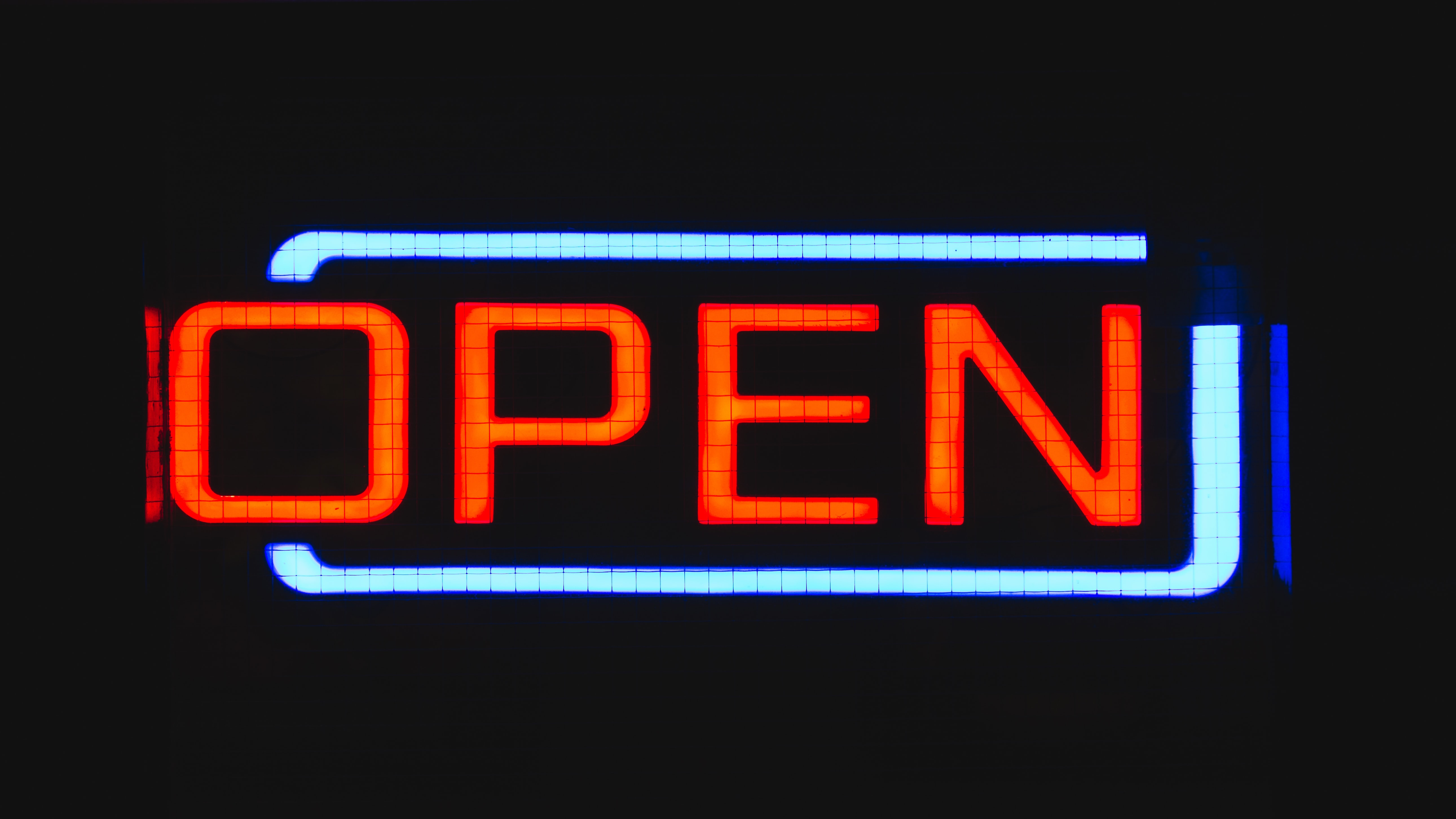 "A bright red and blue neon reads ""open"""