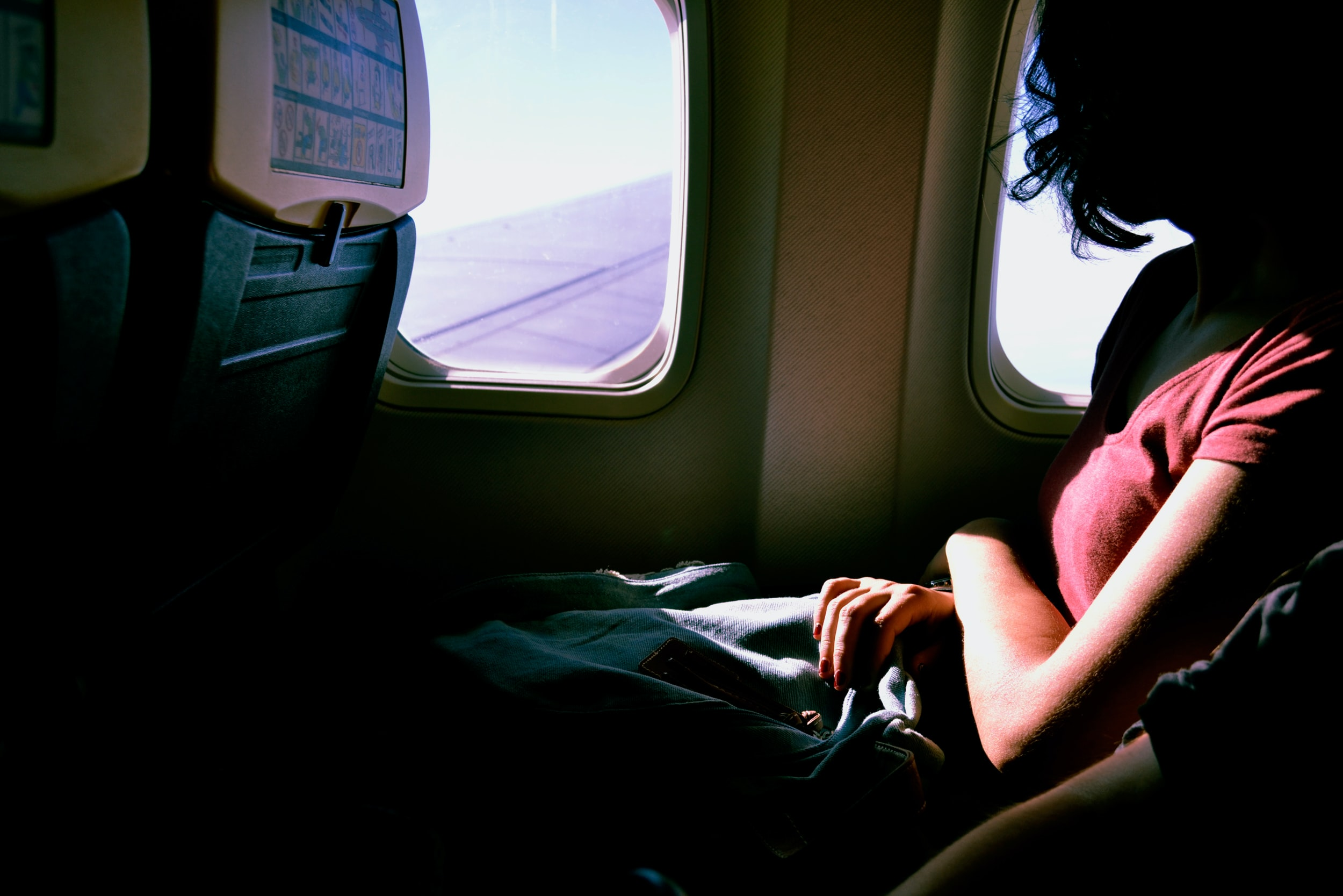 The inside of an airplane with a woman looking out the window