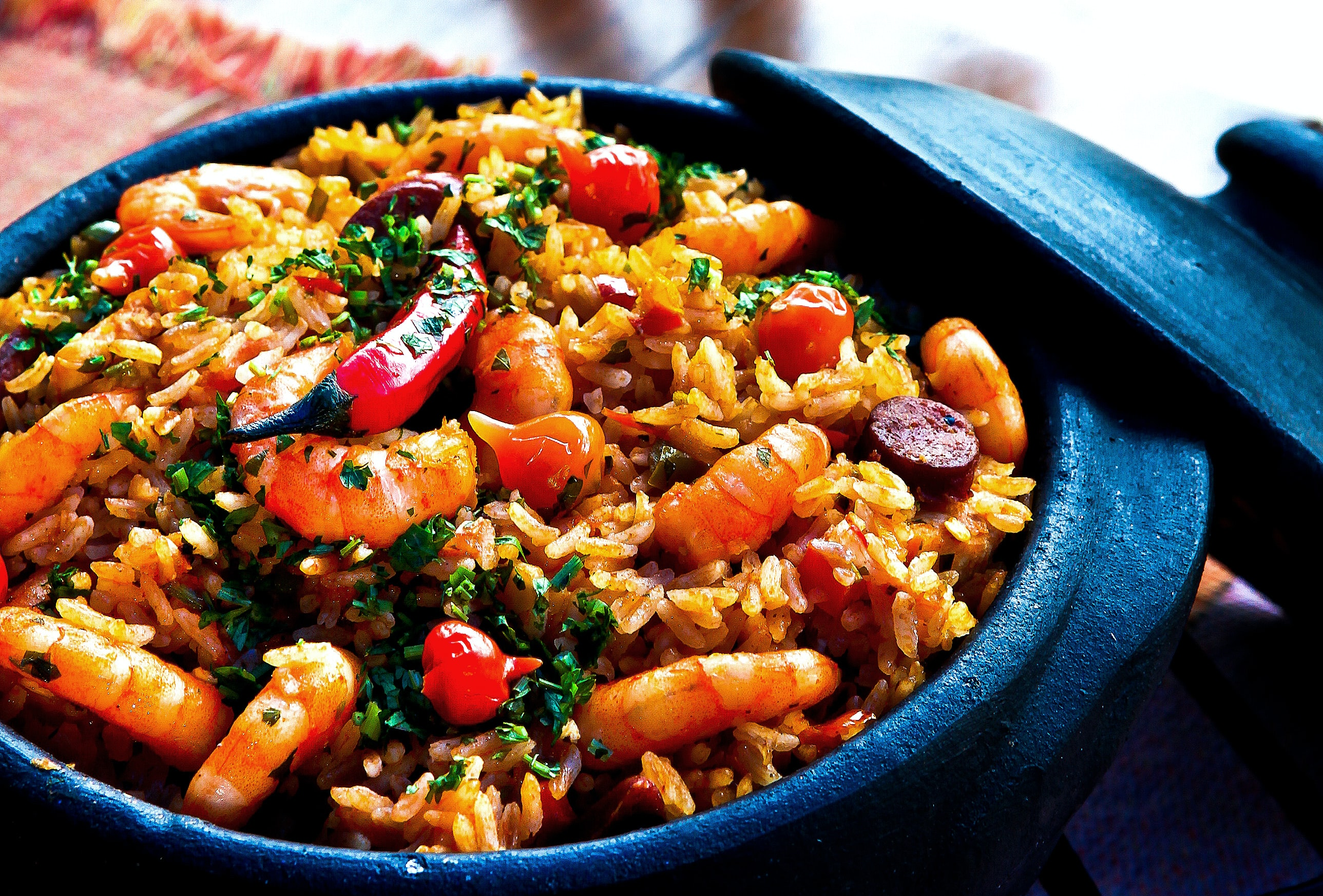 Pot of Spanish paella with shrimp, rice, sausage, and peppers for dinner