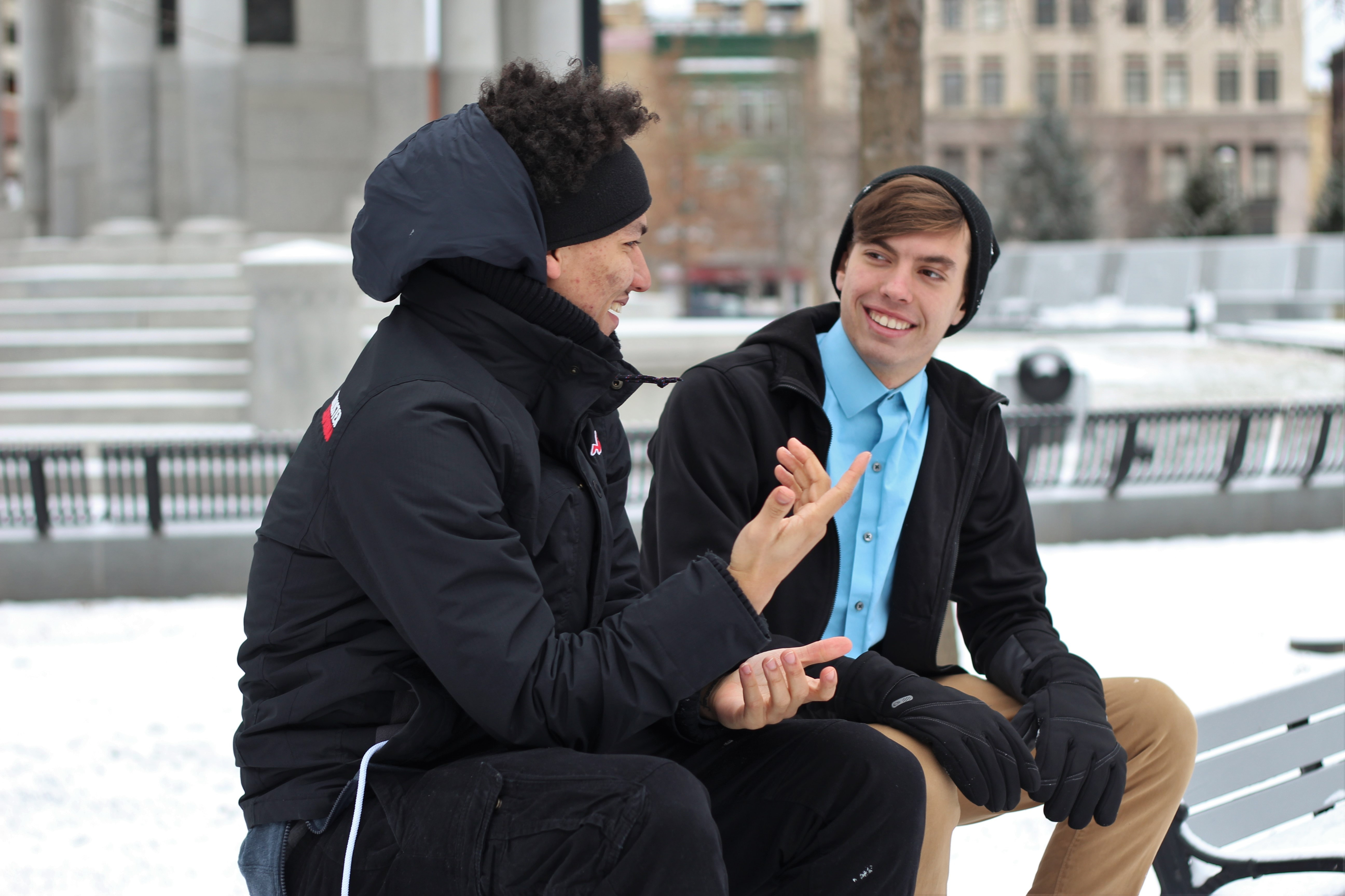 Two guys talking to each other while sitting on a bench in a snowy park in Scranton