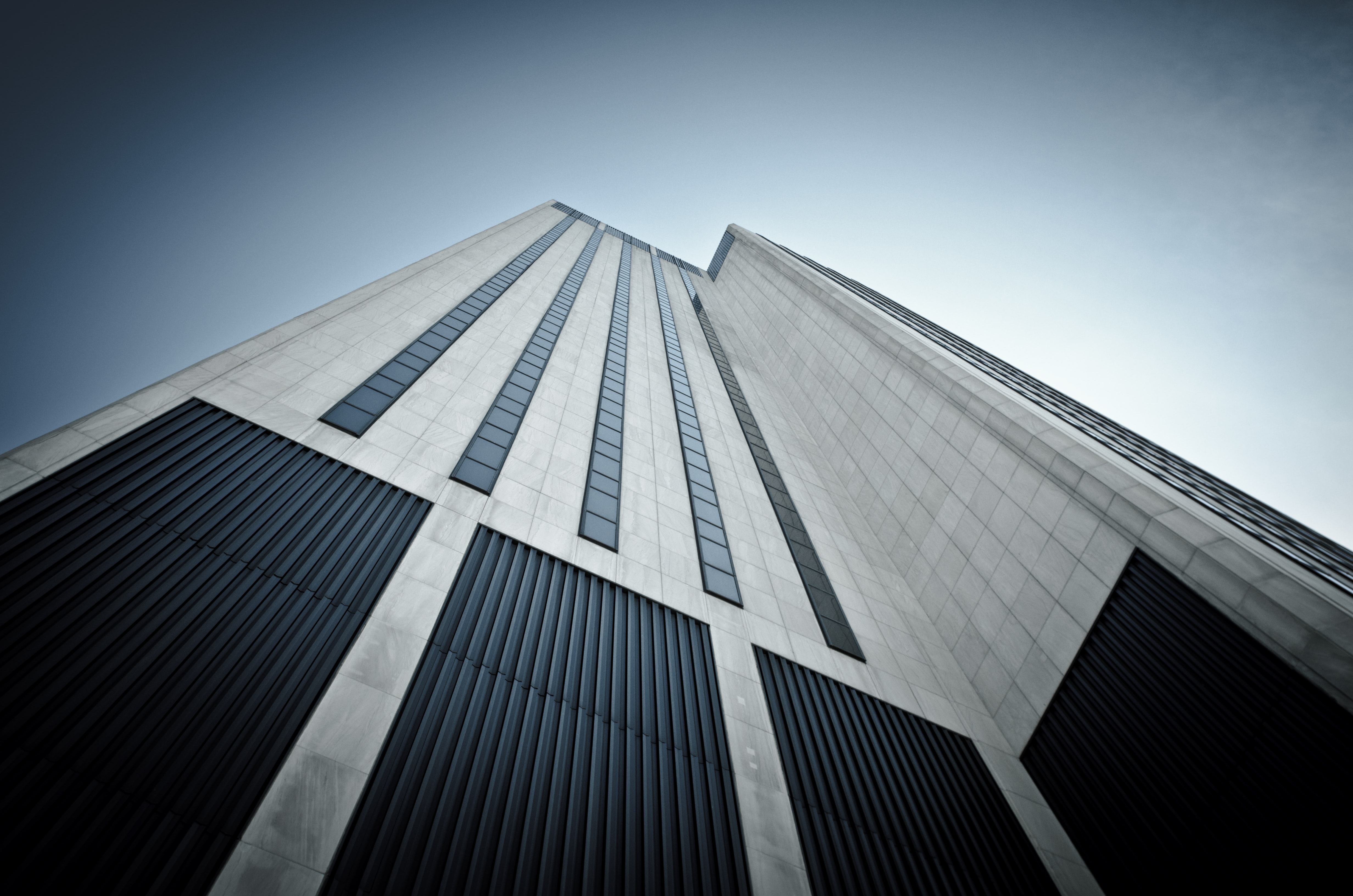 A low-angle shot of a white tiled skyscraper facade with small windows