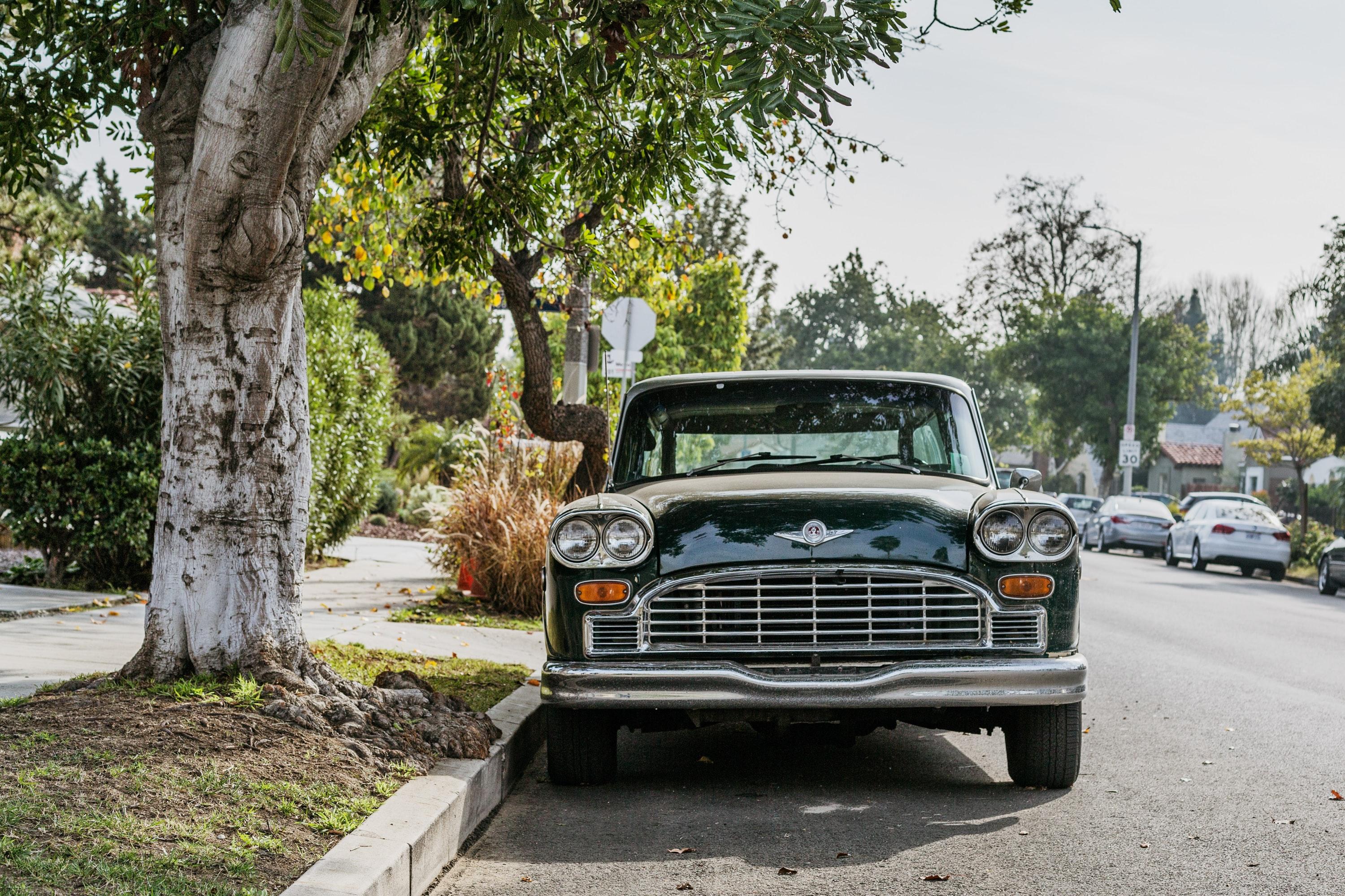 A vintage car parked on a street under a tree in a residential area