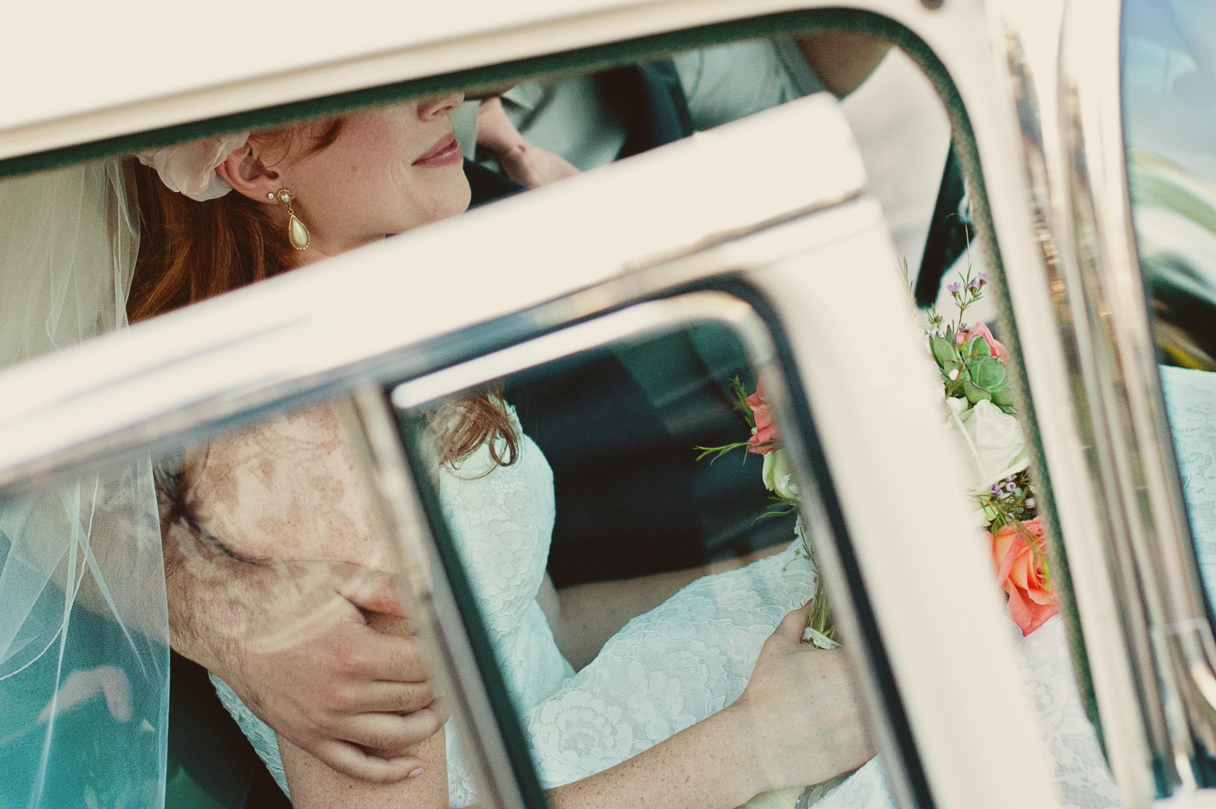 Bridal couple inside a car prepares for their honeymoon