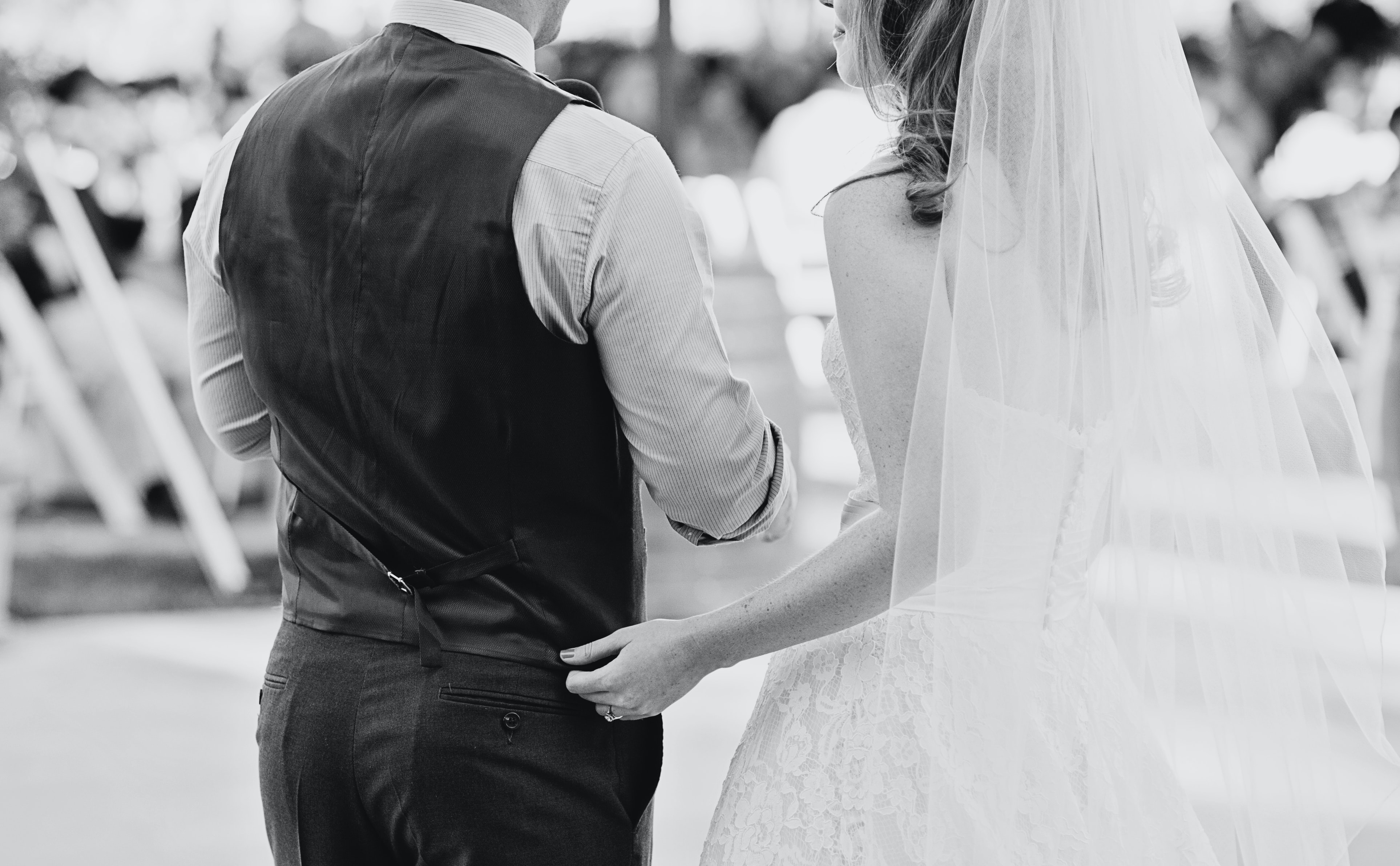 Black and white shot from behind of bride touching groom