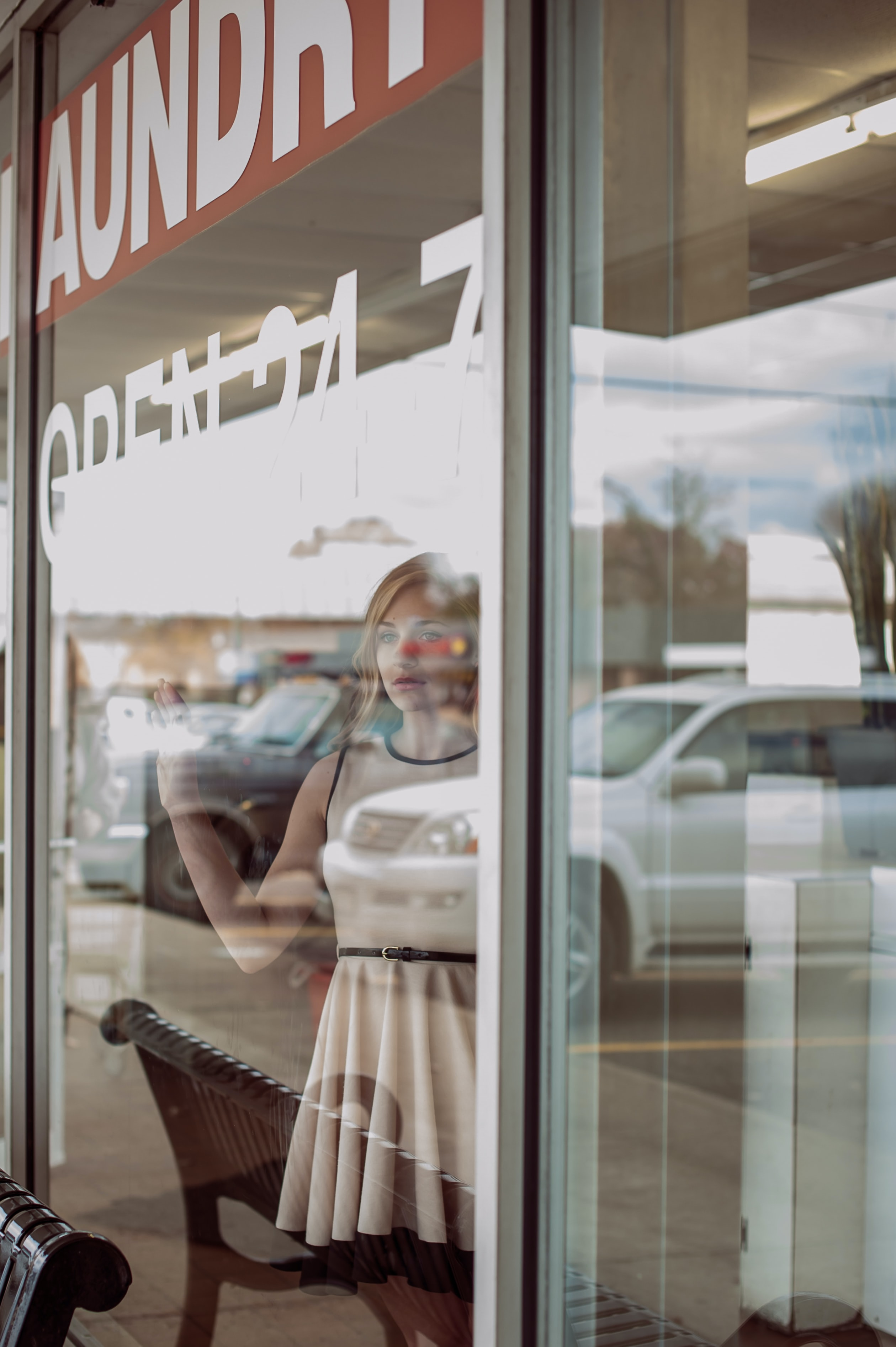 A woman in a white dress is looking out the window of a laundromat.