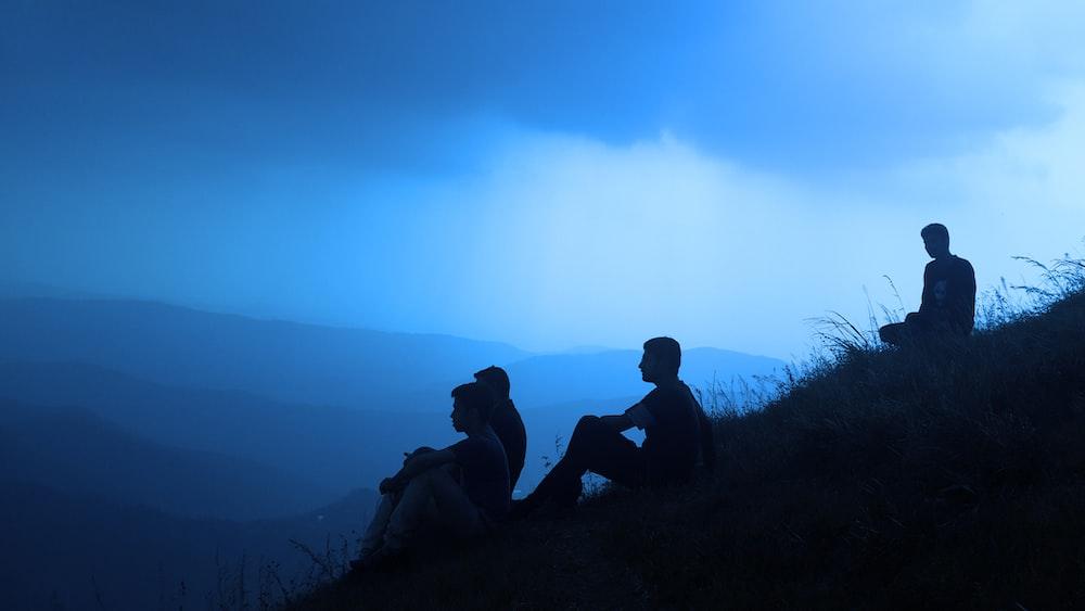 silhouette of men sitting on mountain