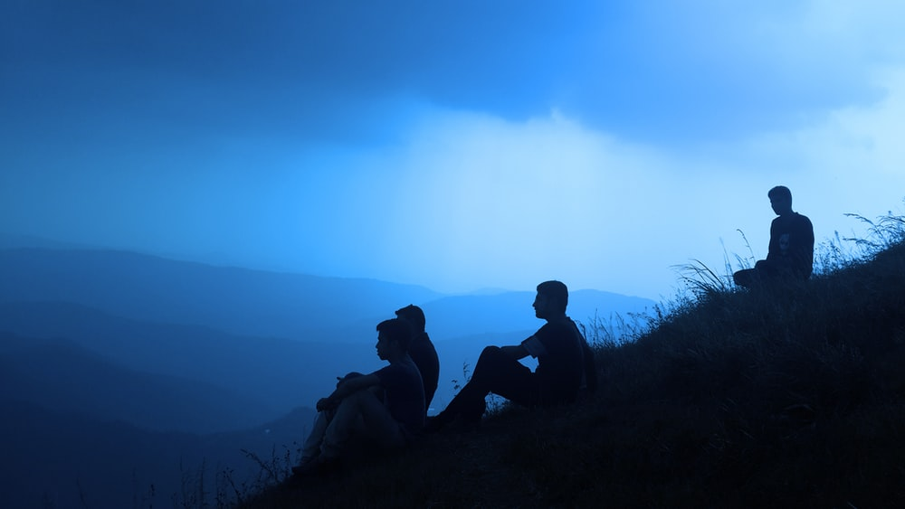 silhouette of men sitting on mountain