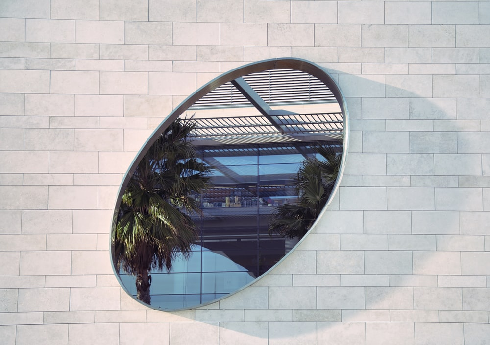 oval mirror on white brick pathway